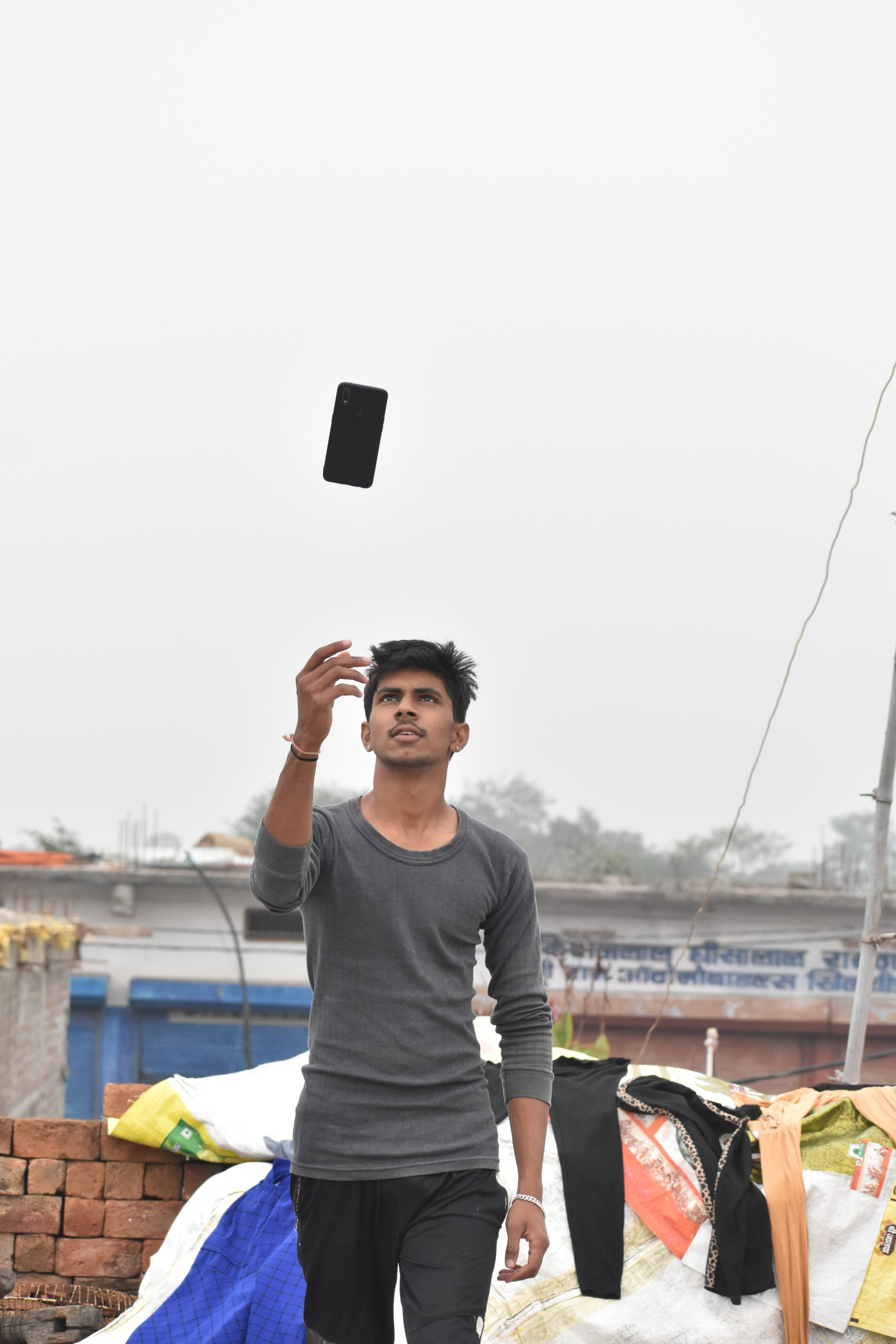 A boy tossing his phone in air