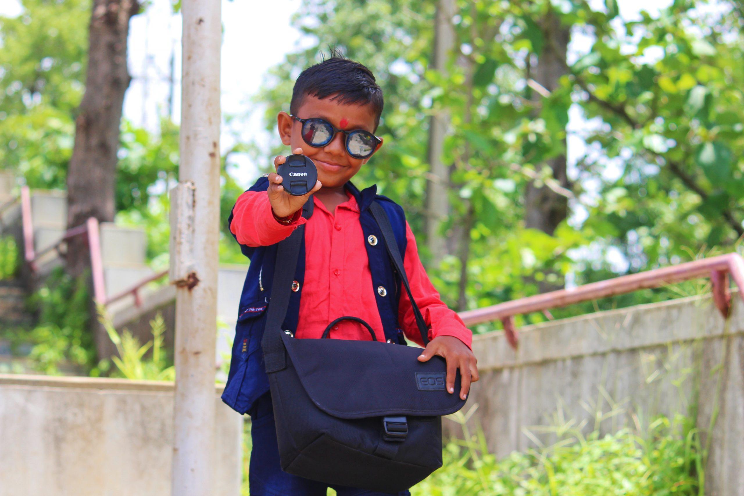 A little boy with lens cap
