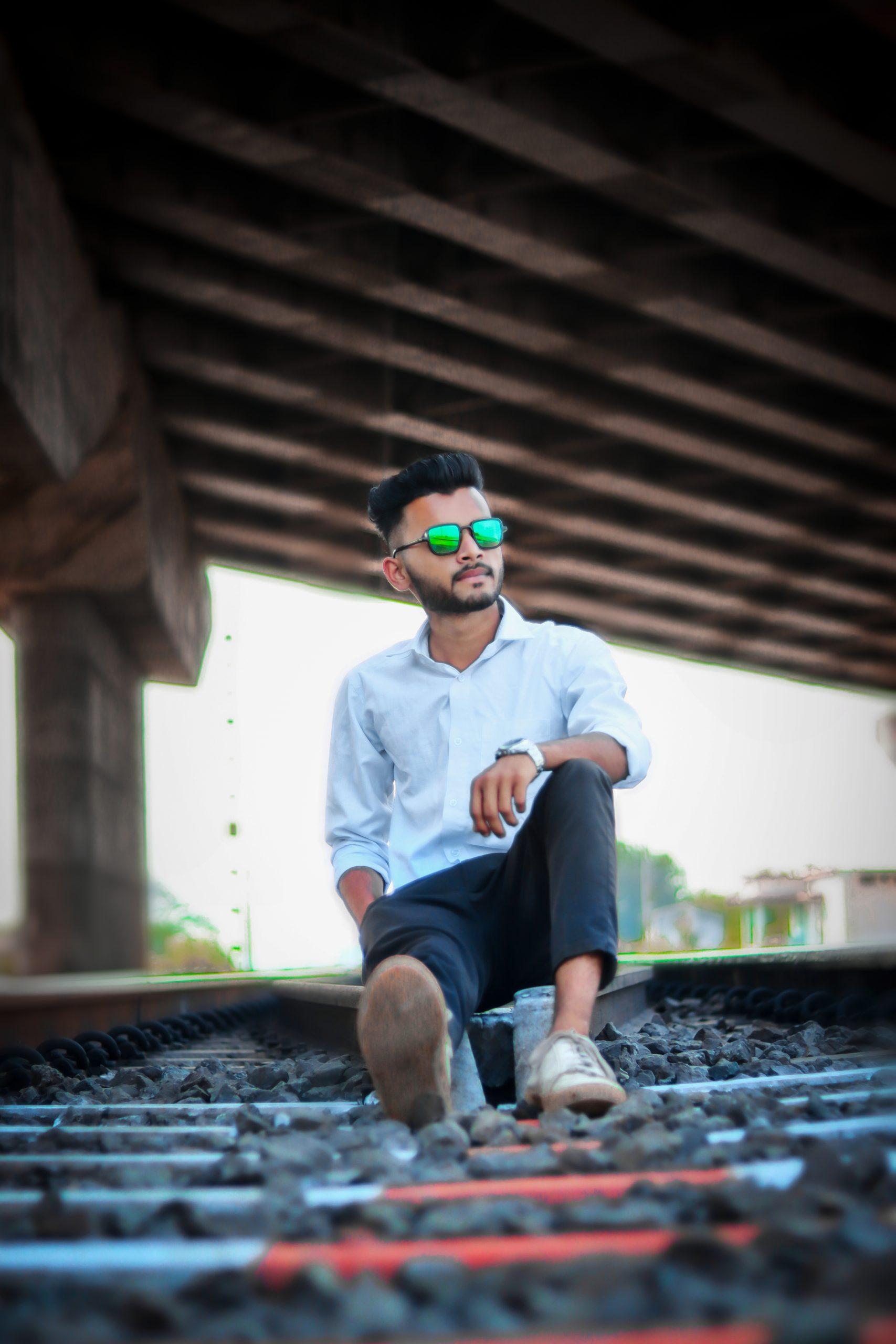 A male model sitting on railway track