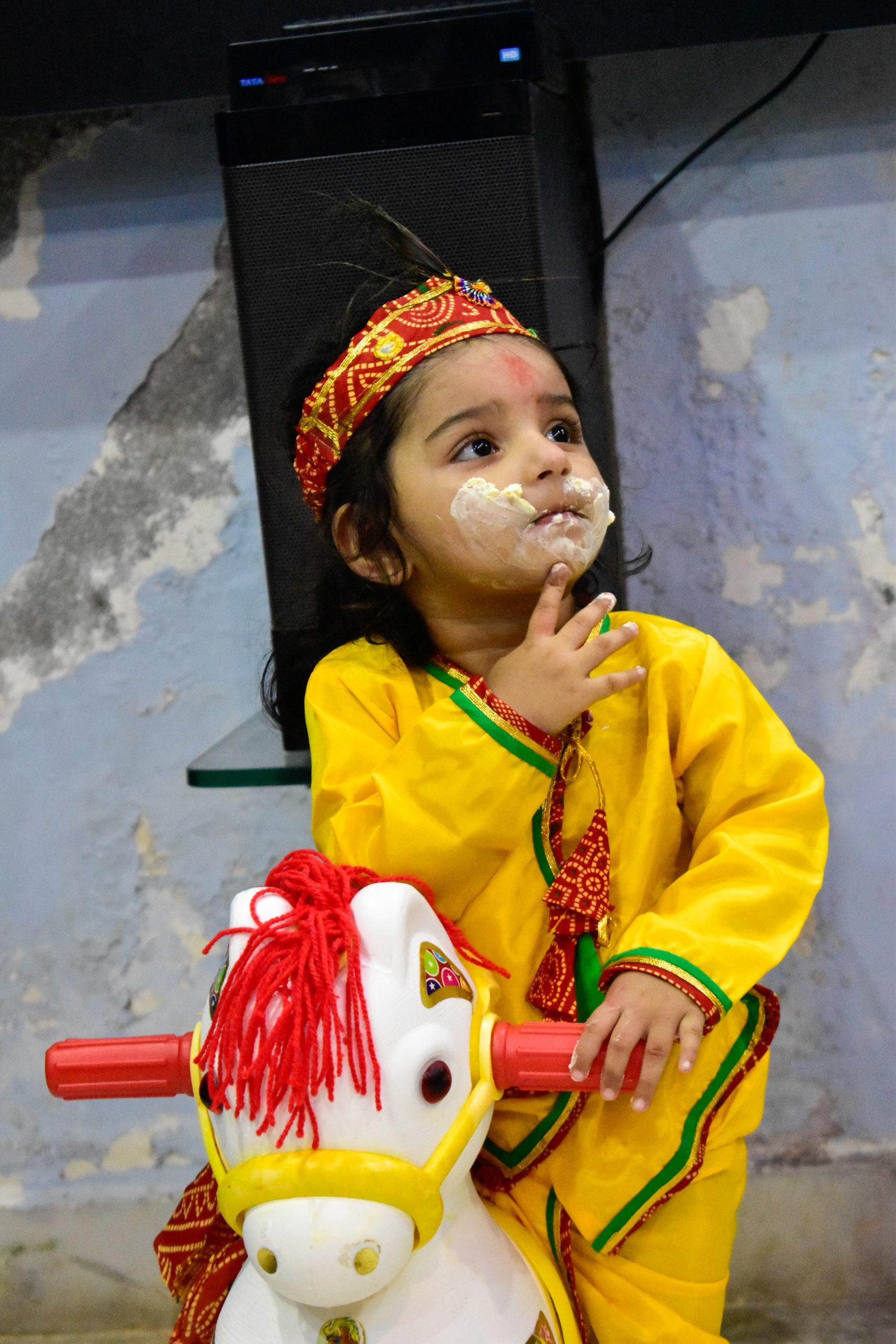 Boy dressed Krishna eating butter