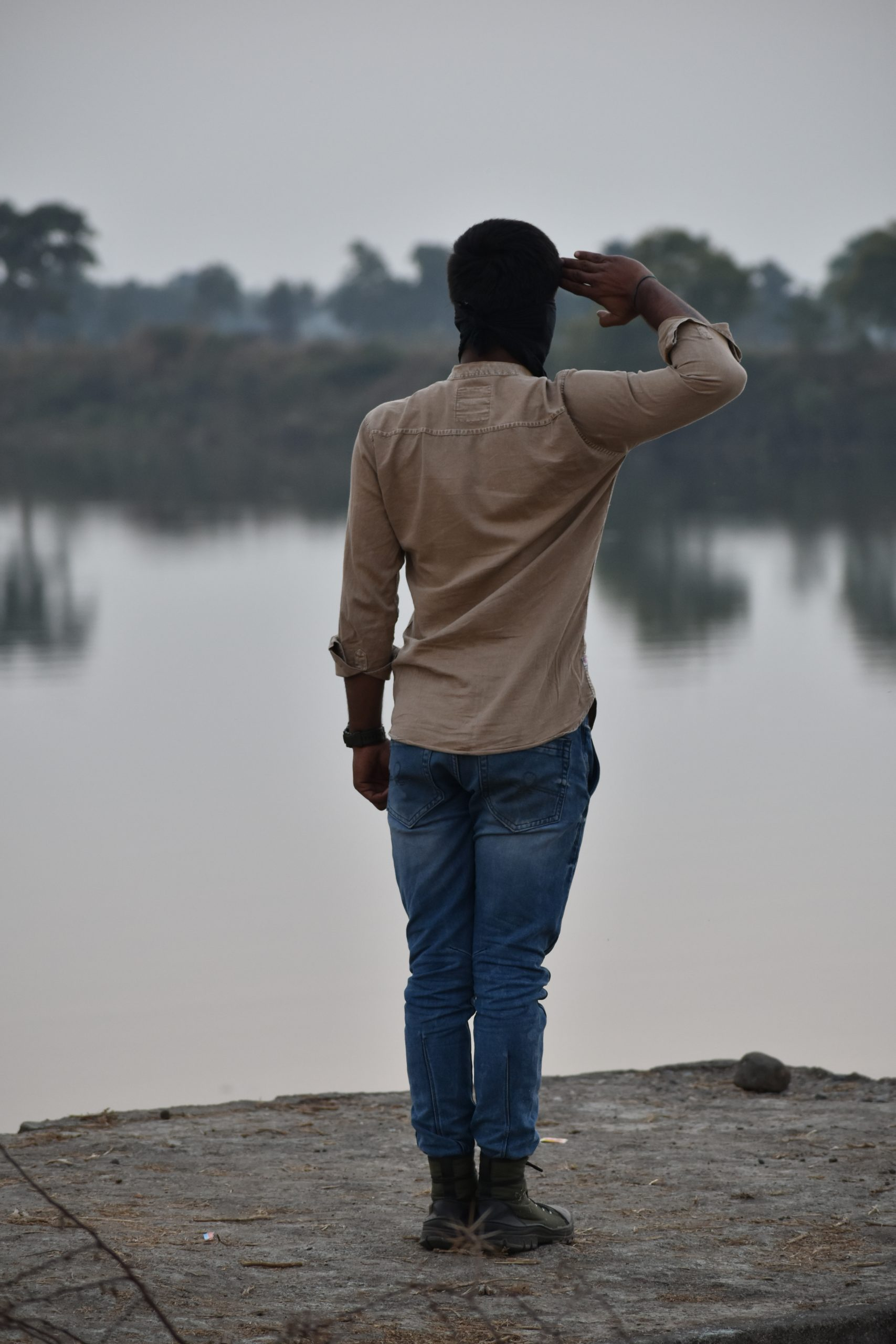 Boy giving salute near the river