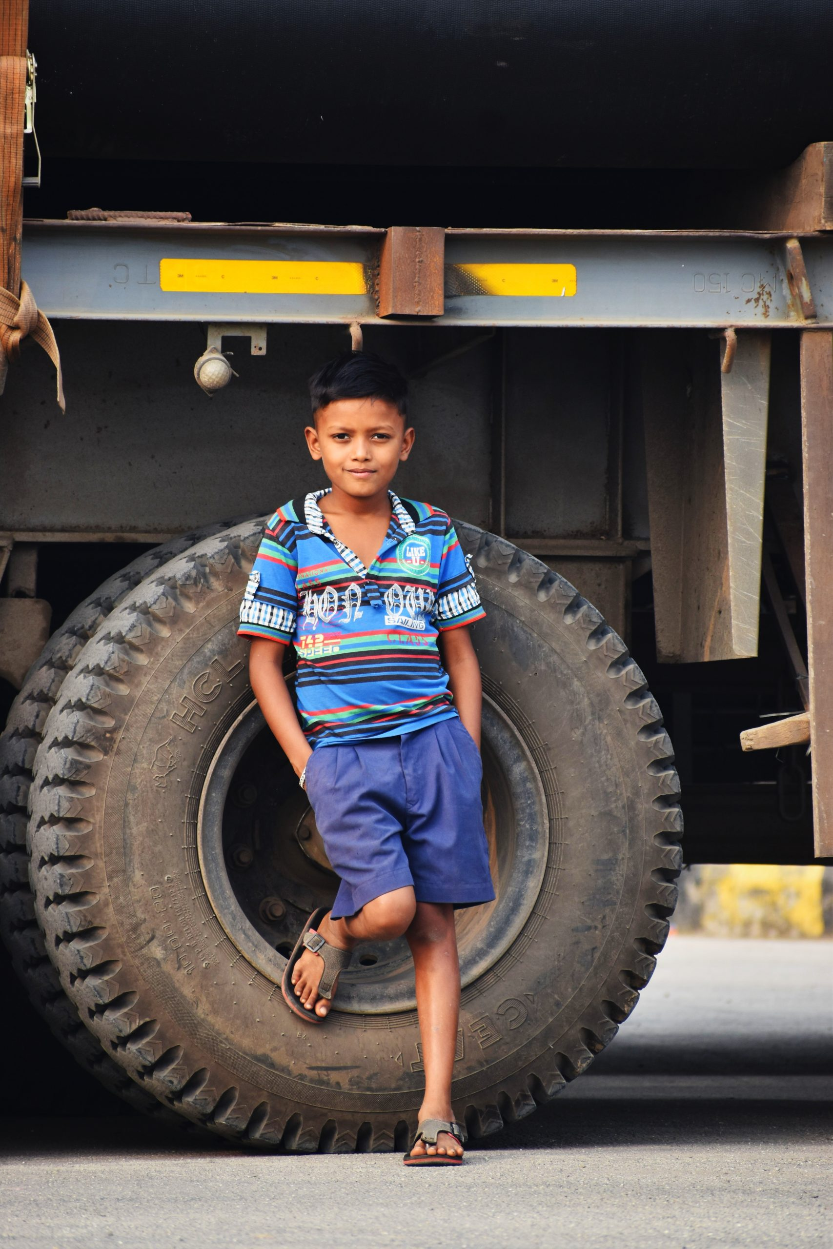 Boy posing against the truck tyres