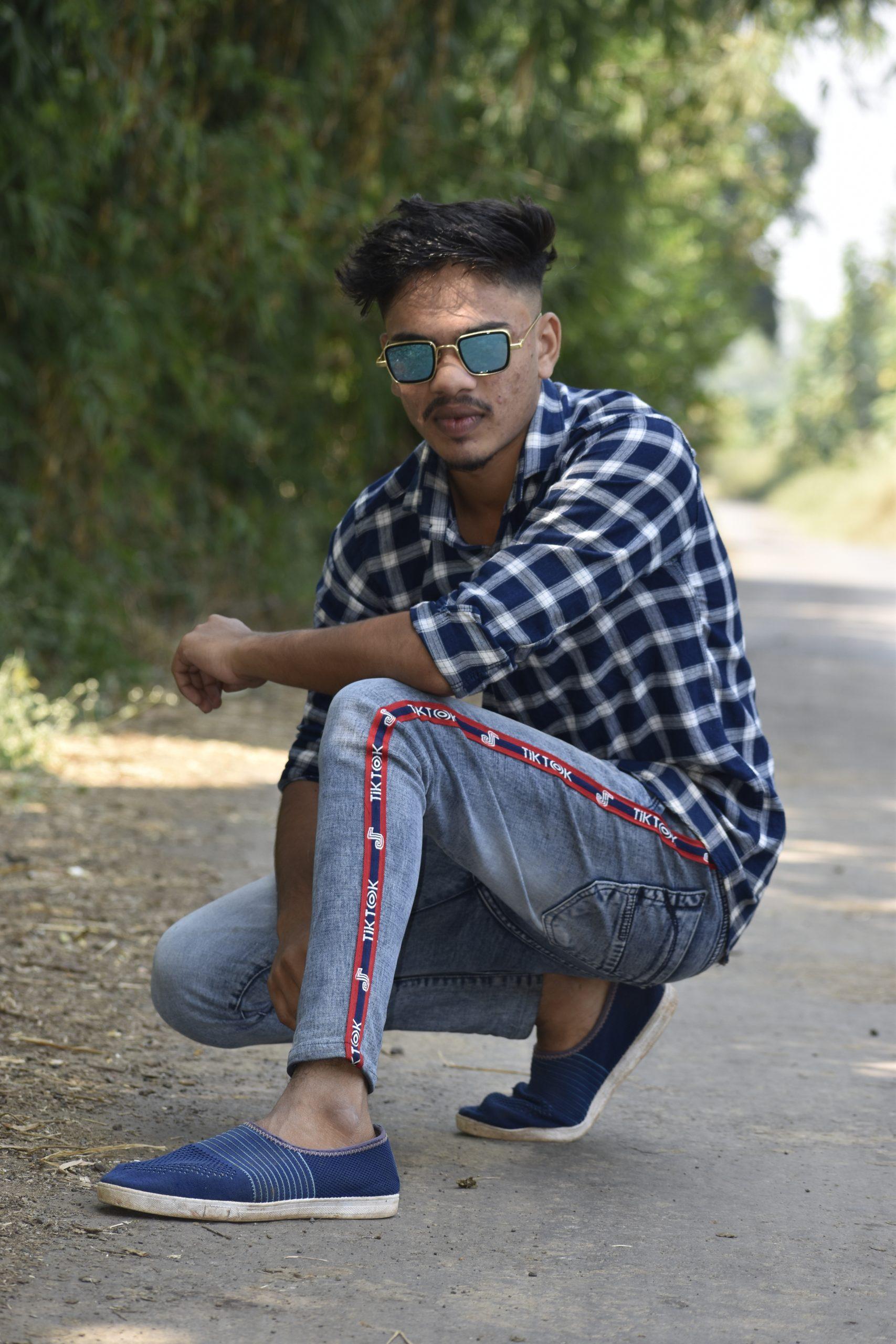 Boy posing on road while sitting