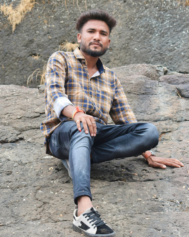 Boy posing while sitting on rock