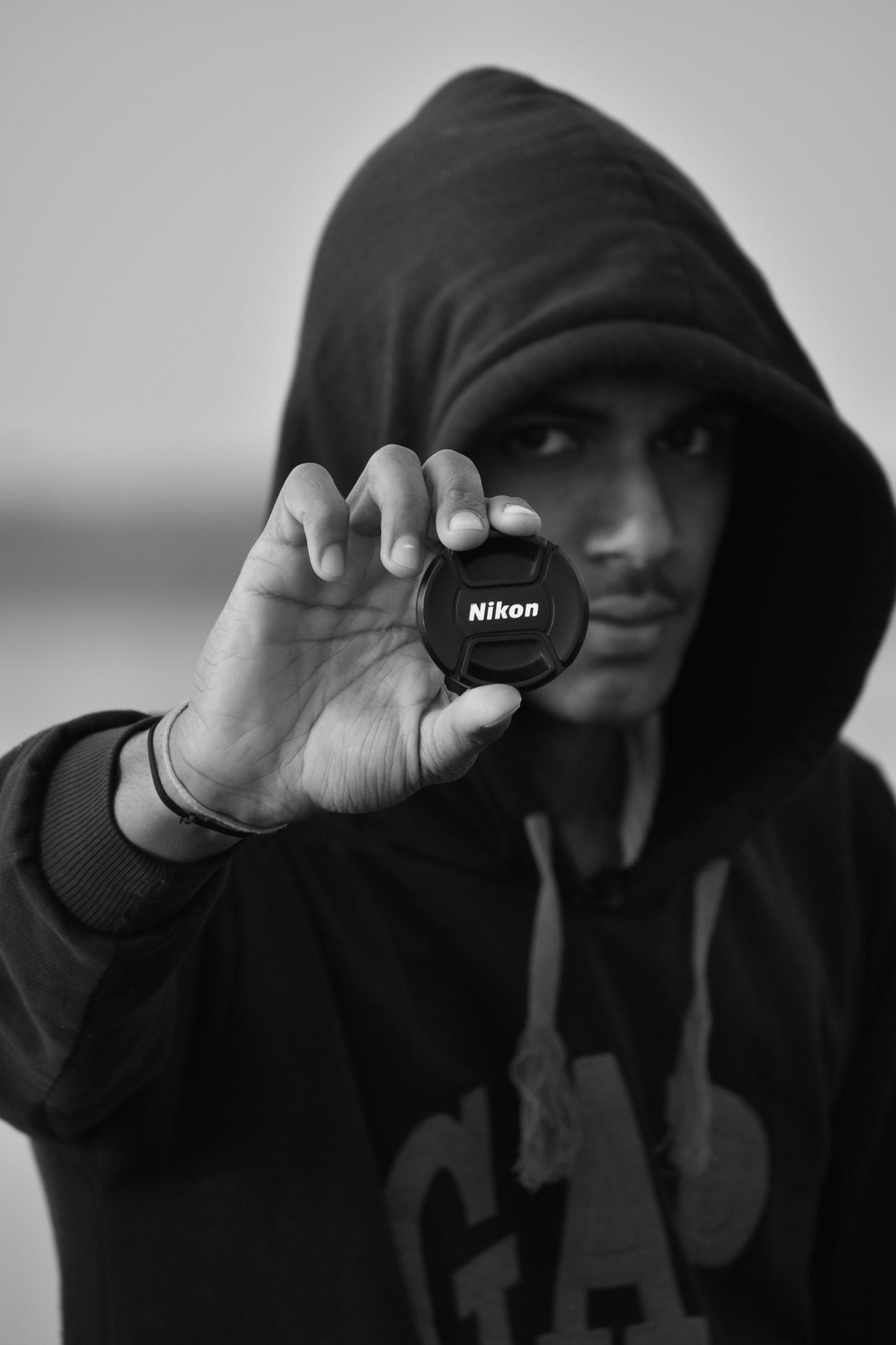 Boy posing with Nikon lens cap