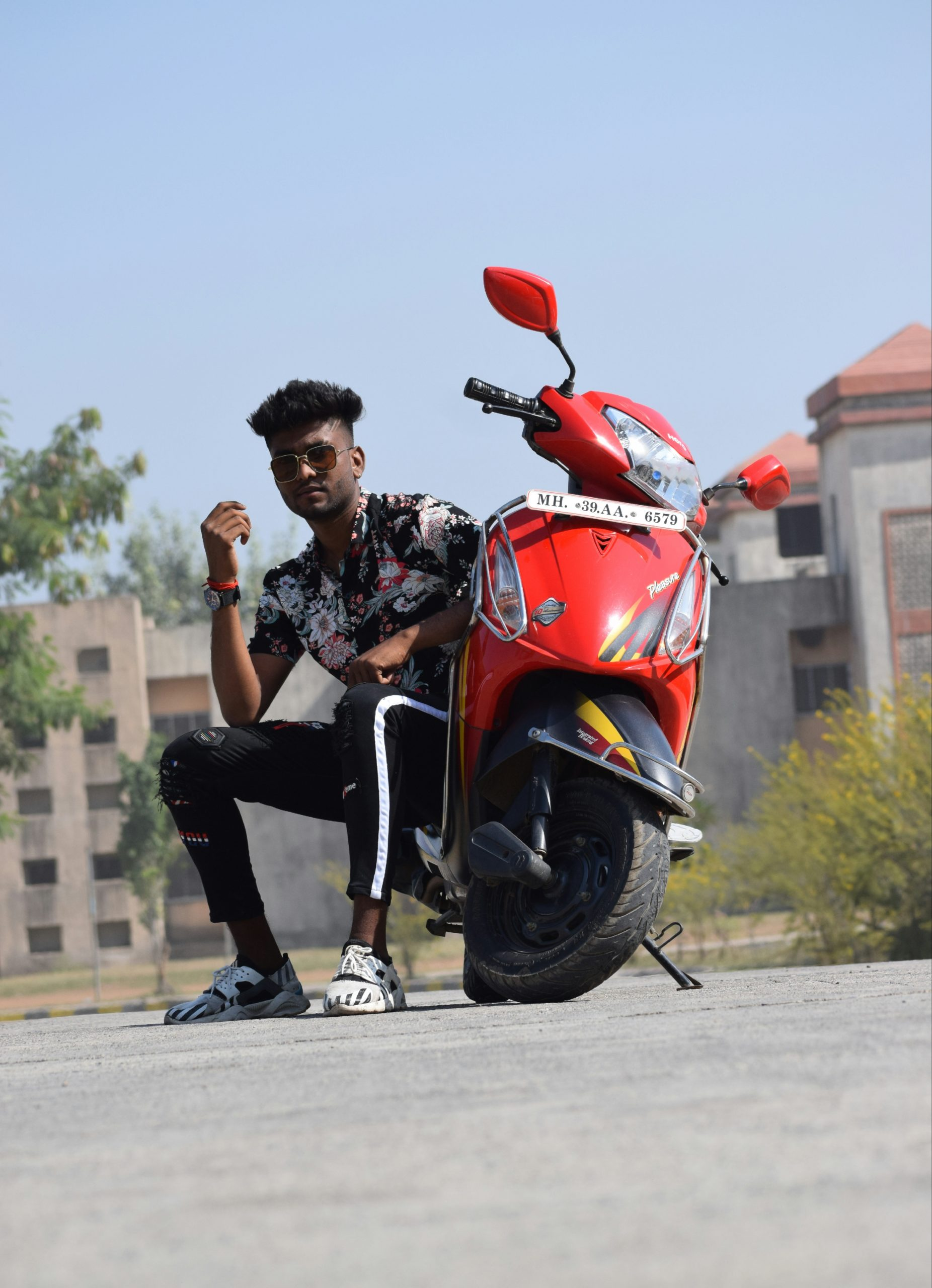Boy posing with scooty on road