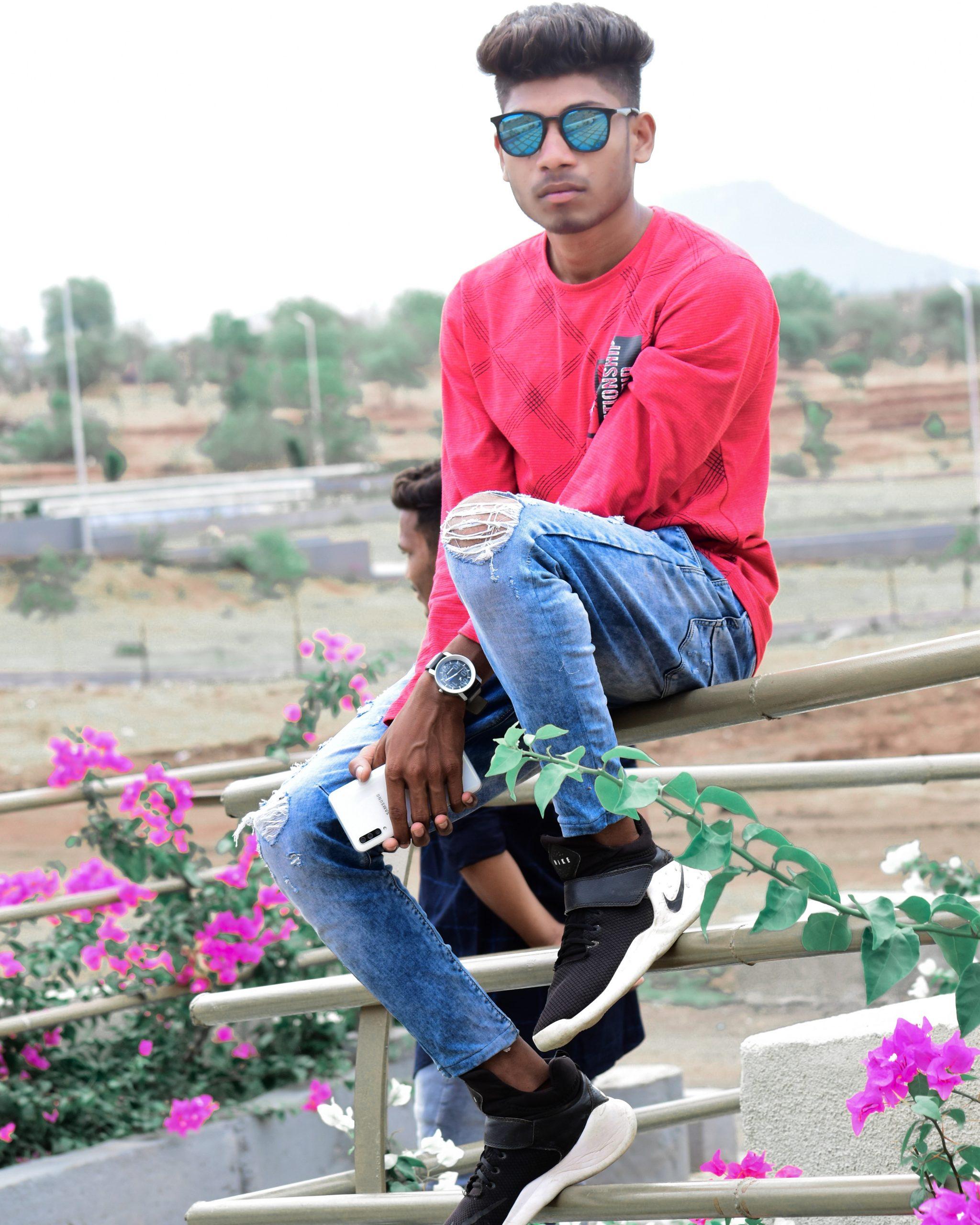 Boy sitting on railing and posing