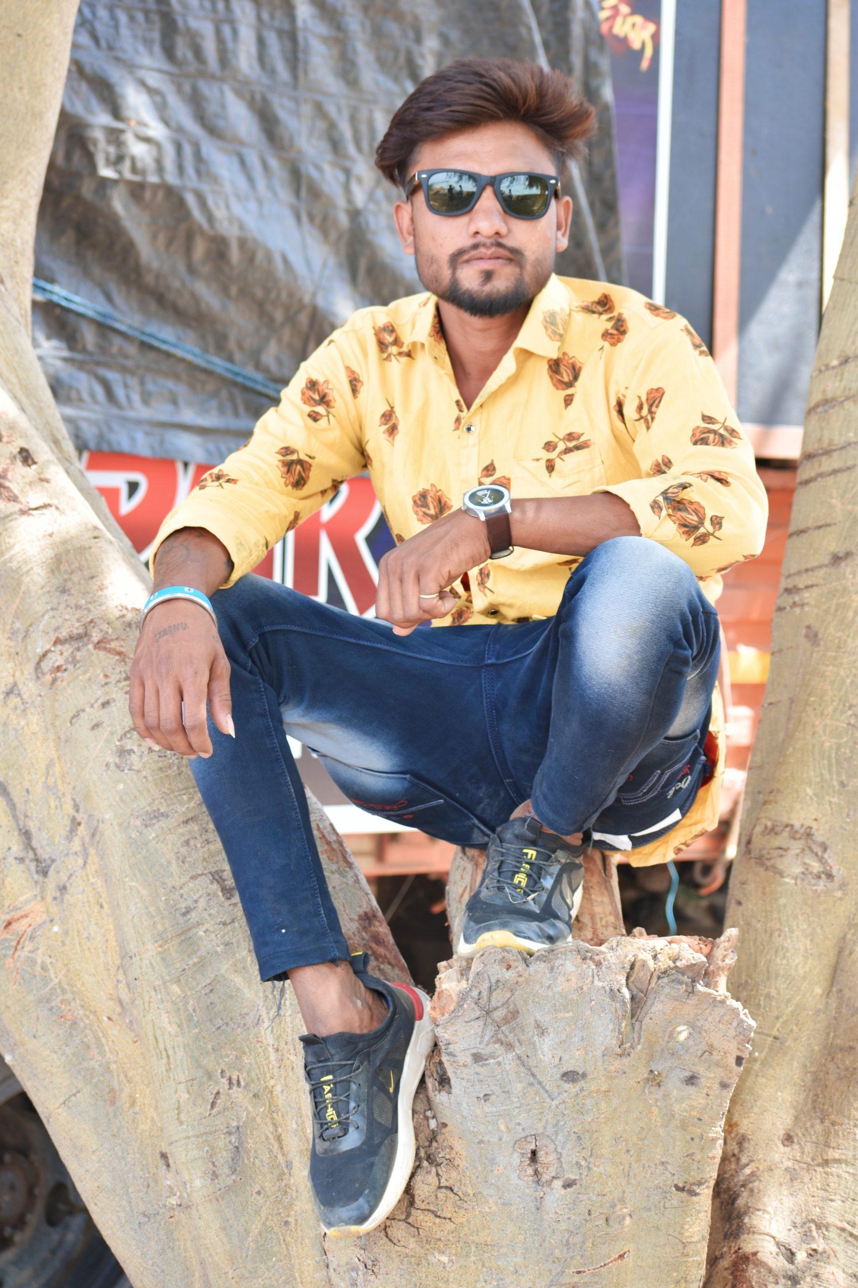 Boy sitting on tree and posing