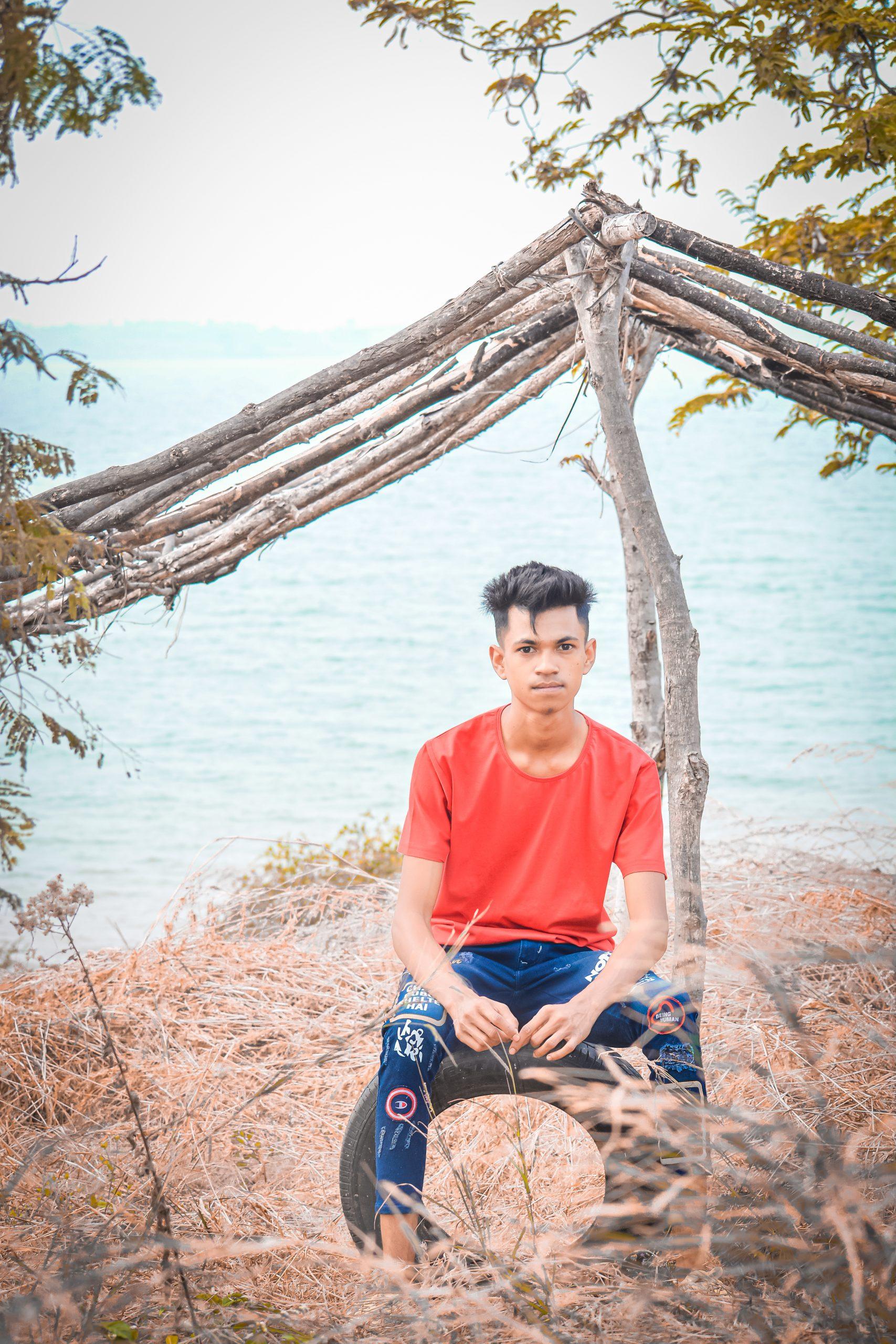 Boy sitting on tyre near the sea