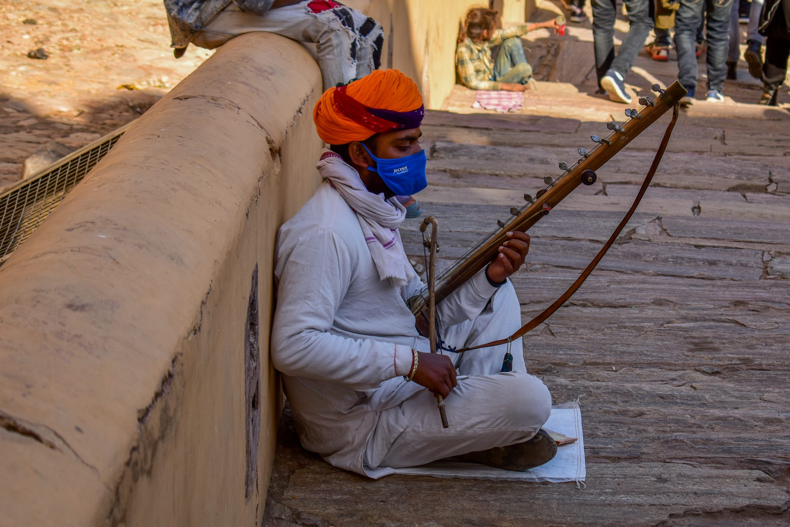 Boy with mask playing music instrument roadside