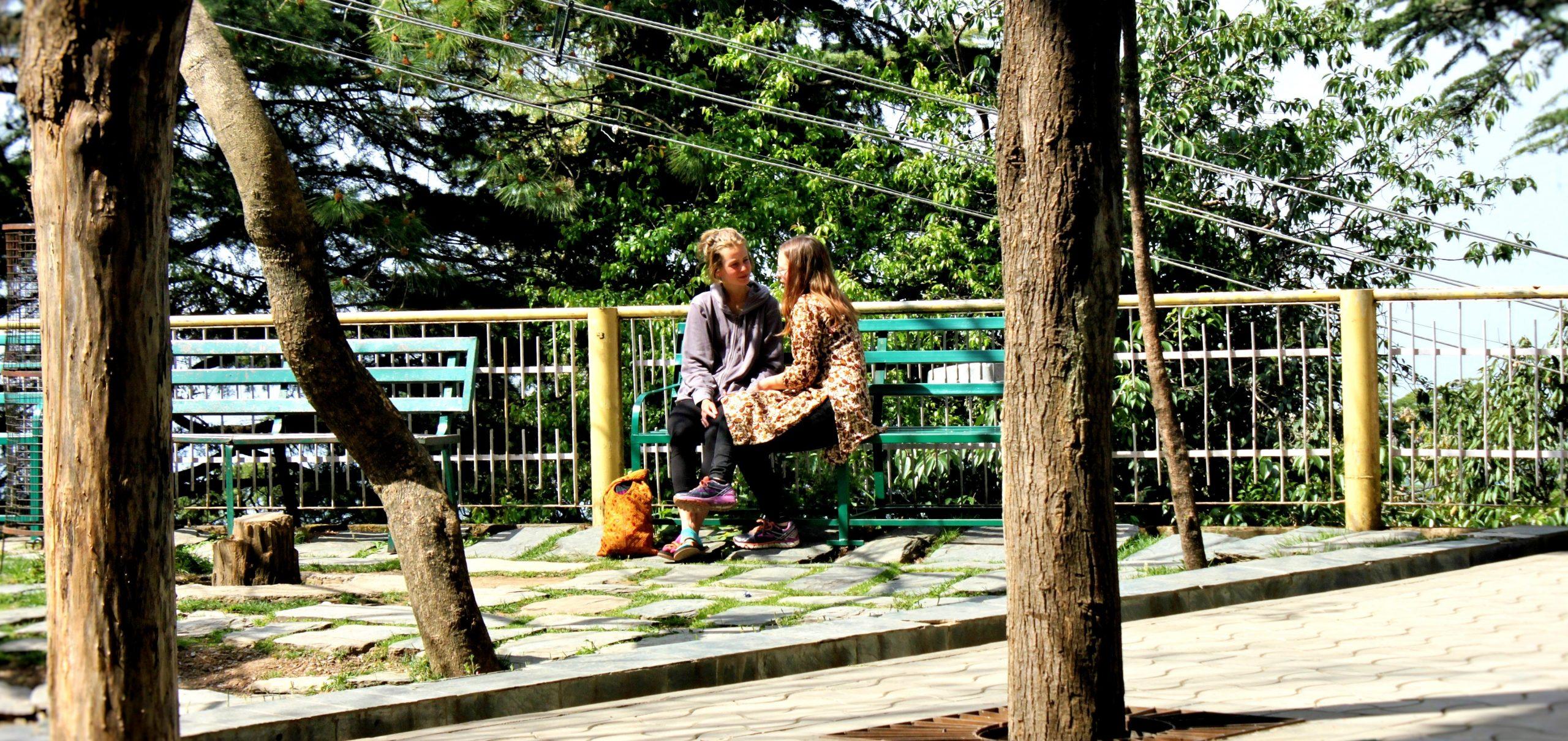 Two girls sitting on bench near railing