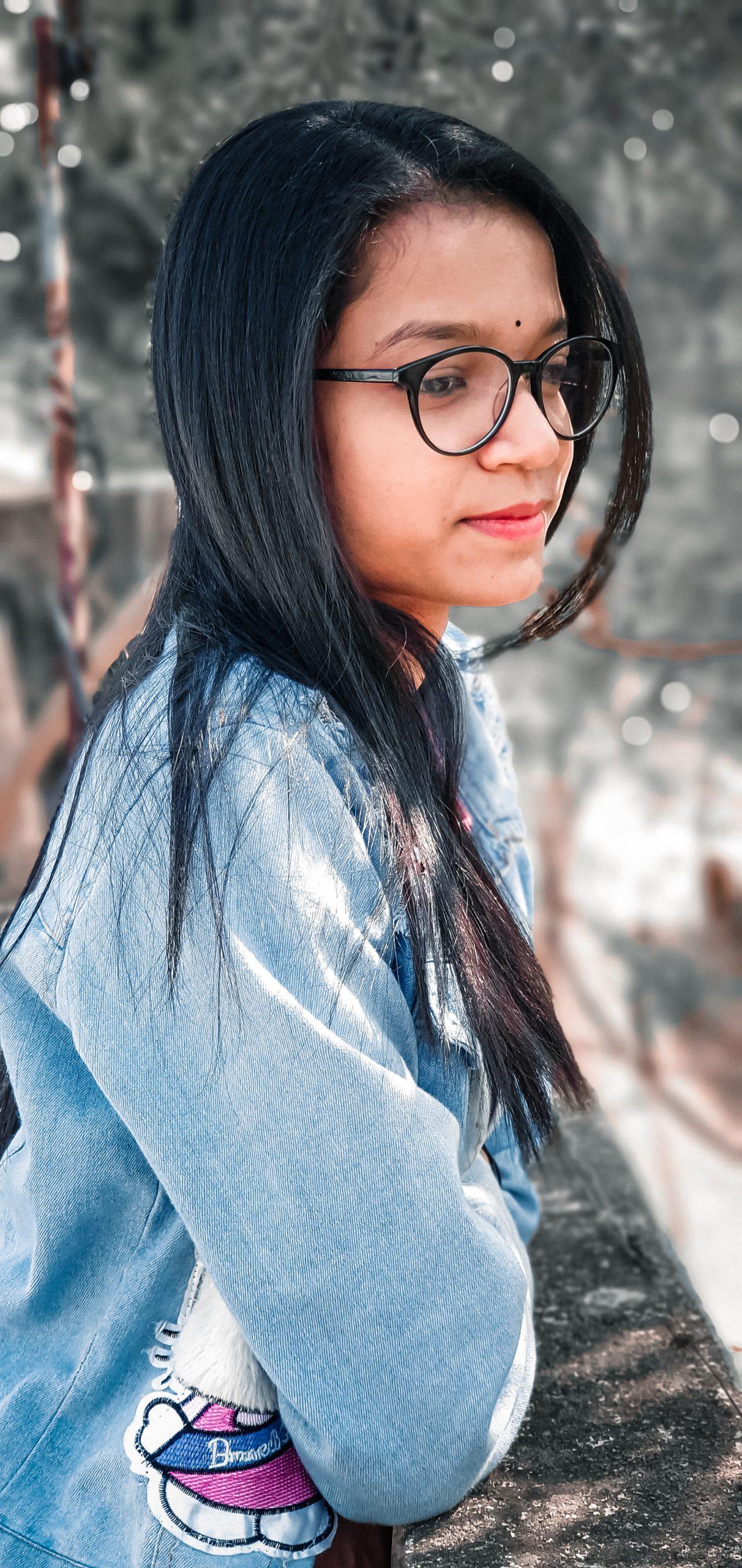 Girl posing near the wall in specs