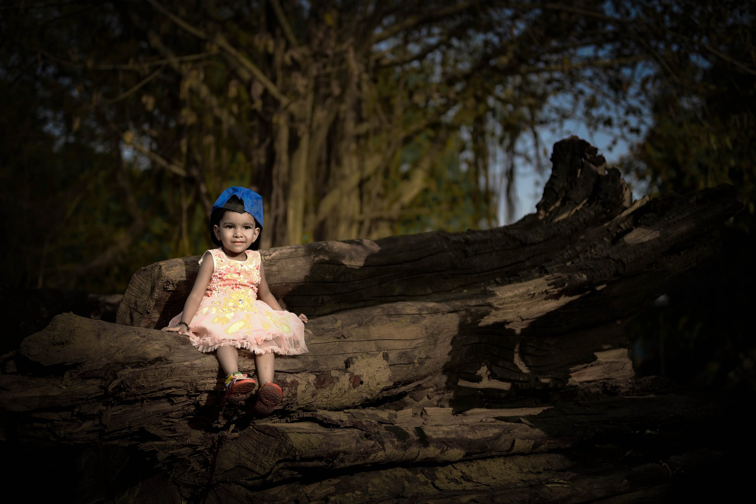 Little girl sitting on tree trunk