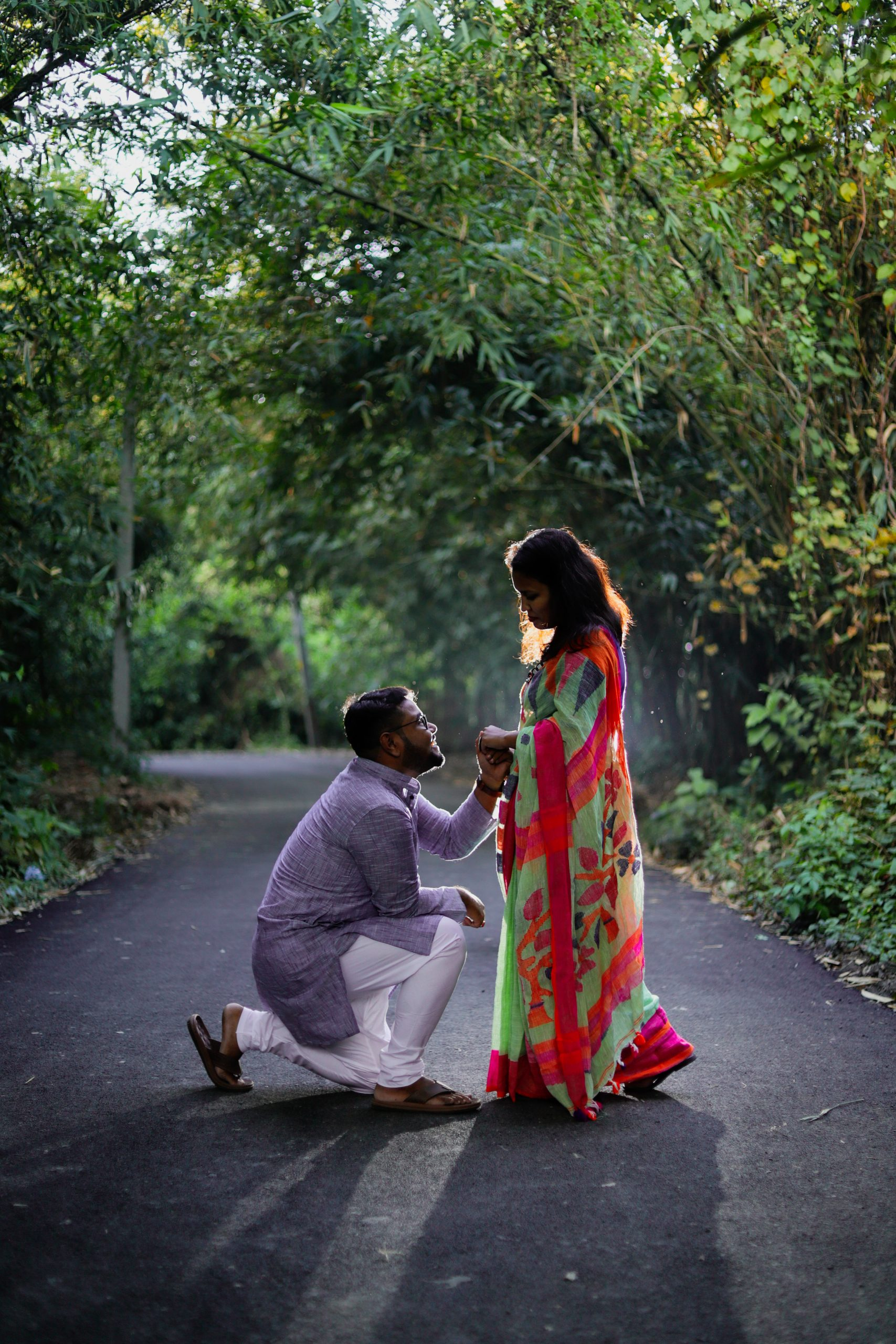 Man proposing girl in the forest road