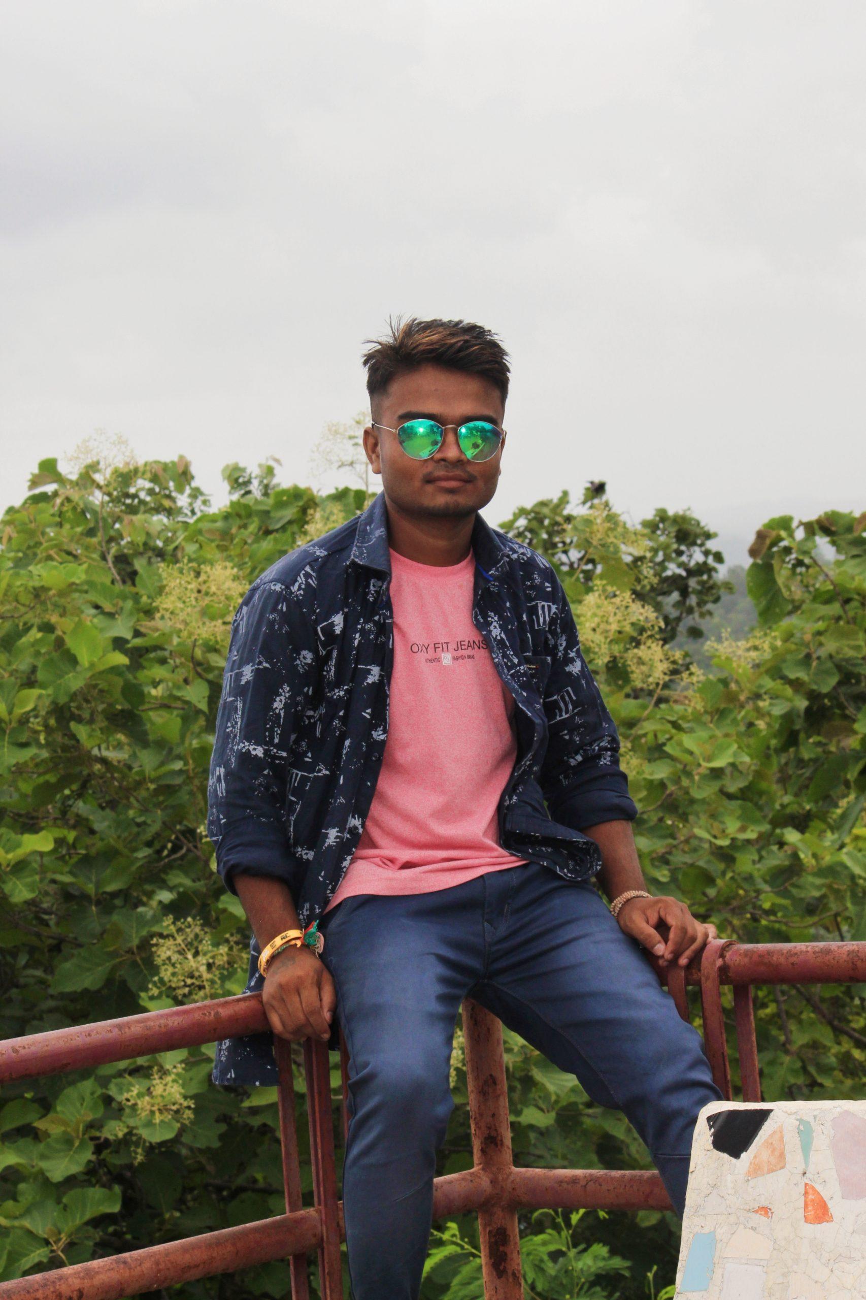 Model posing while sitting on railing