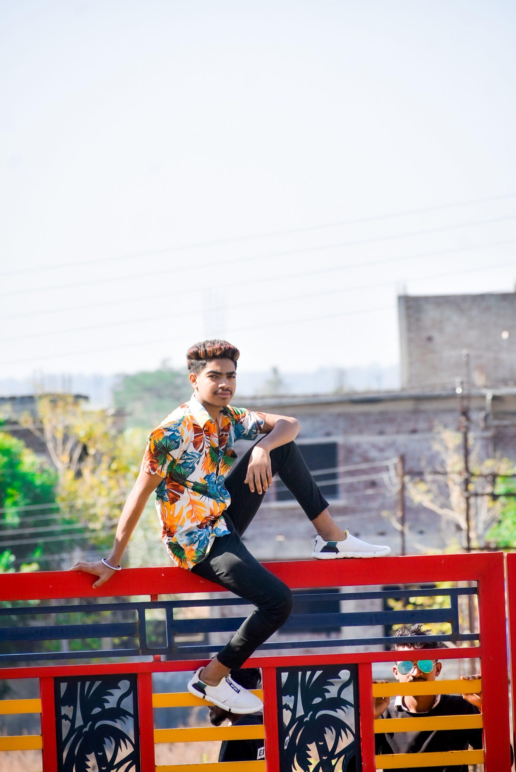 A boy sitting on a railing
