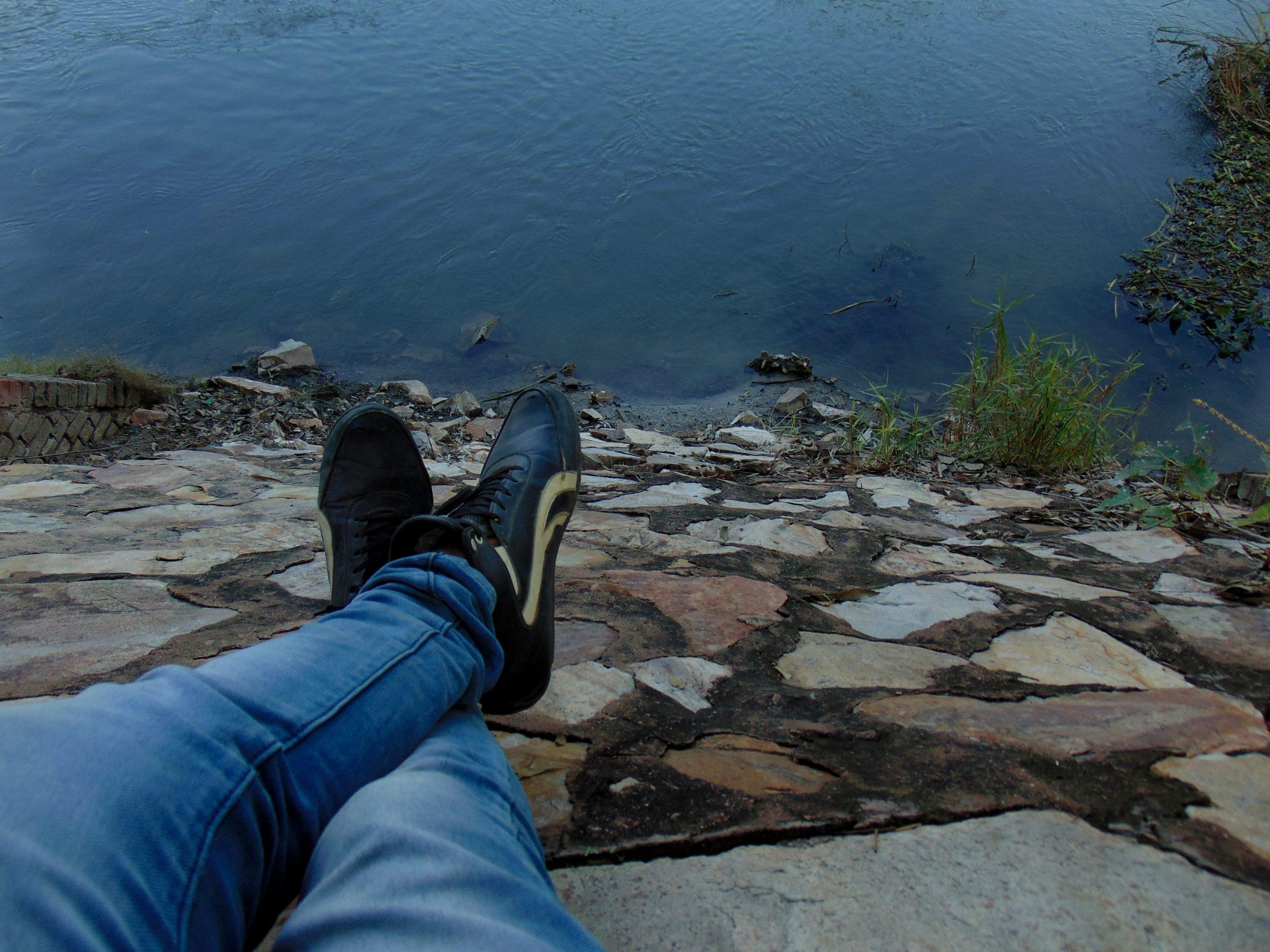 Resting human legs near a lake