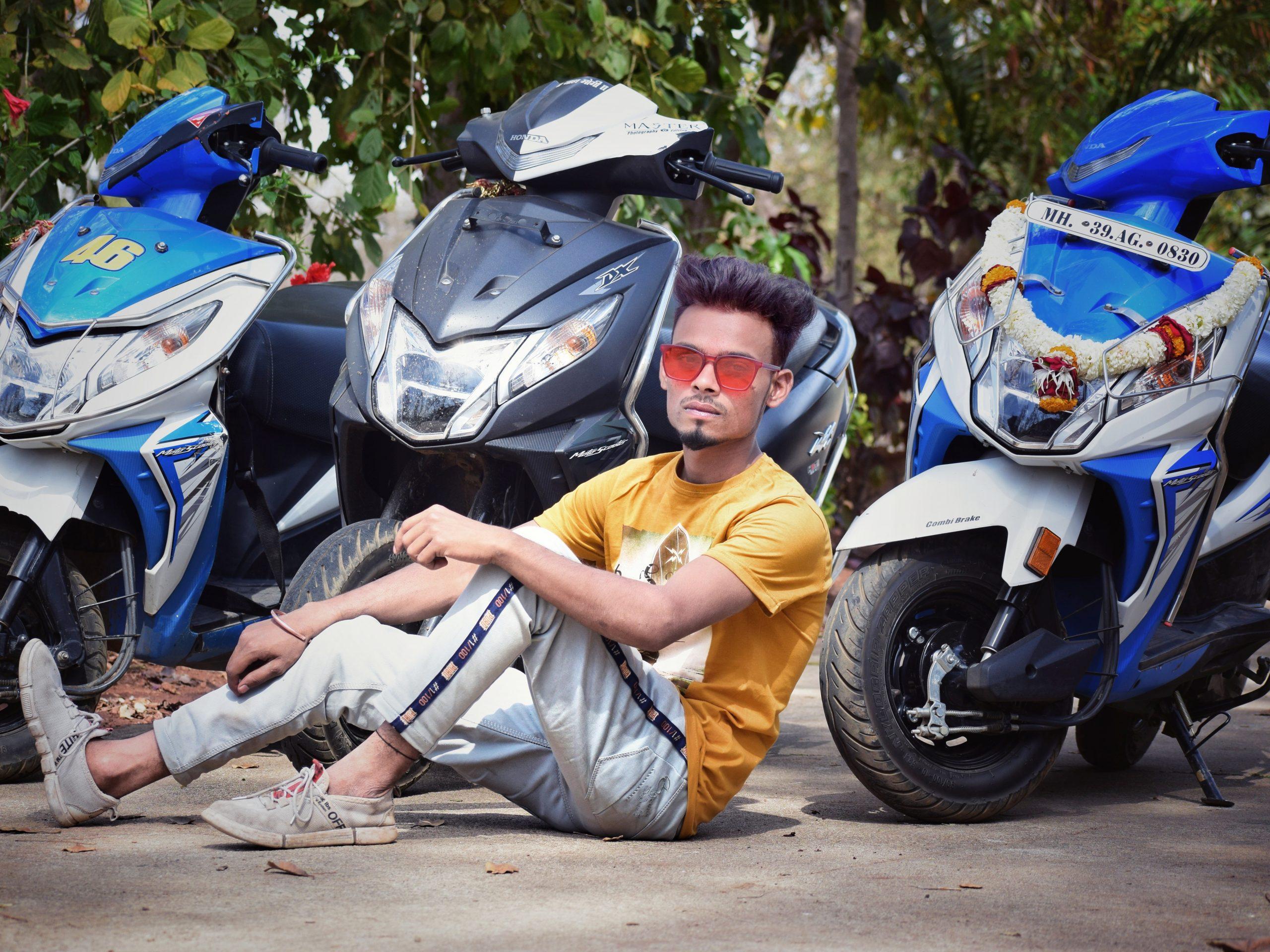 A stylish boy near scooters