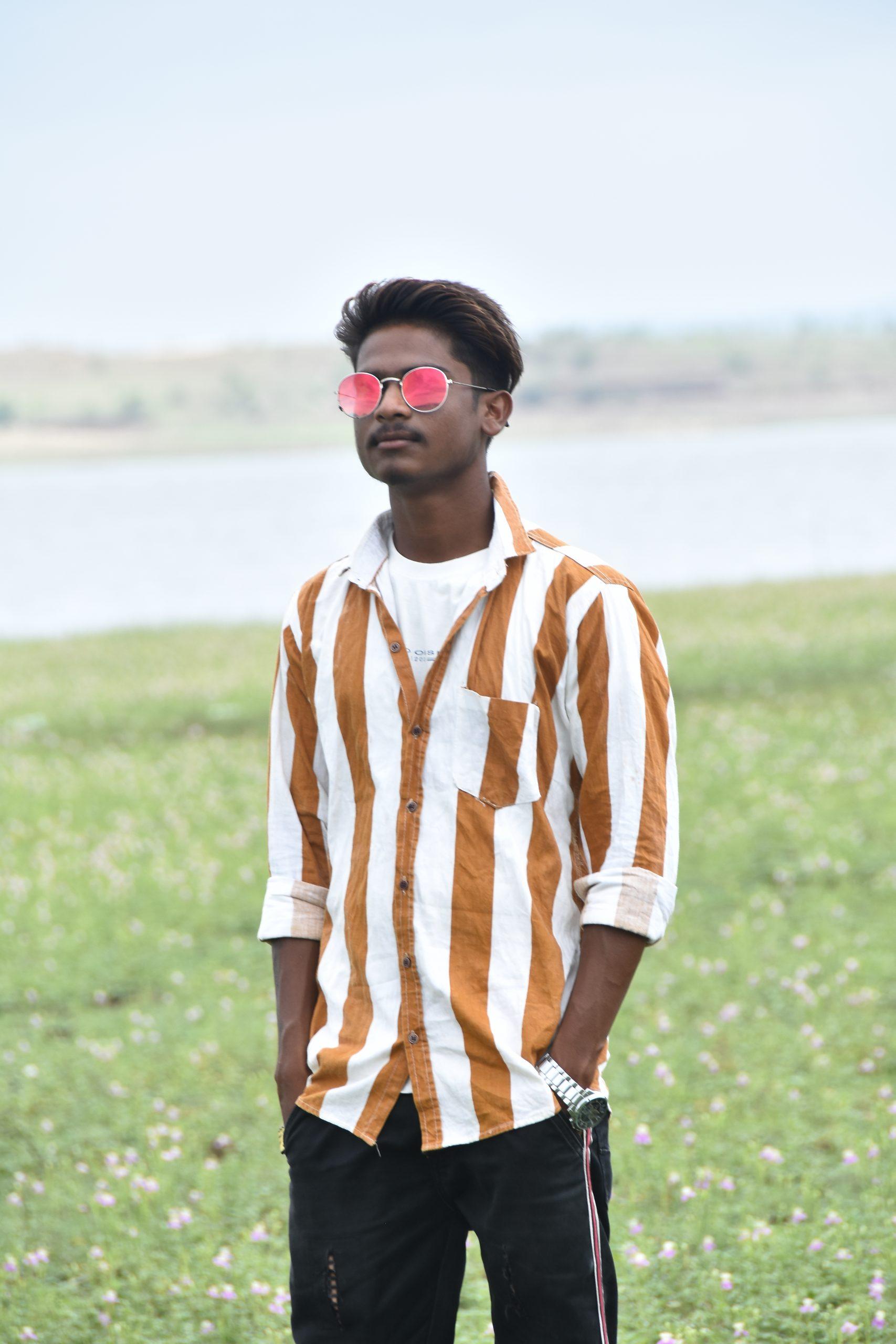 Stylish boy posing in the farm with sunglasses