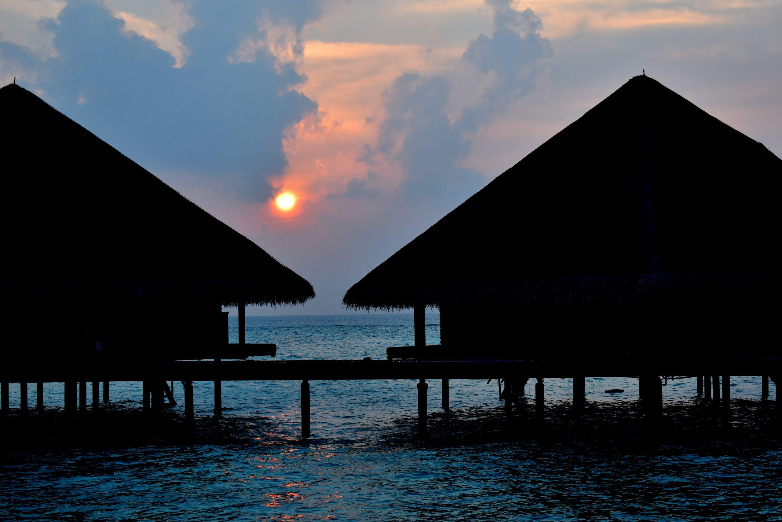 Sunset through a water villa in Maldives