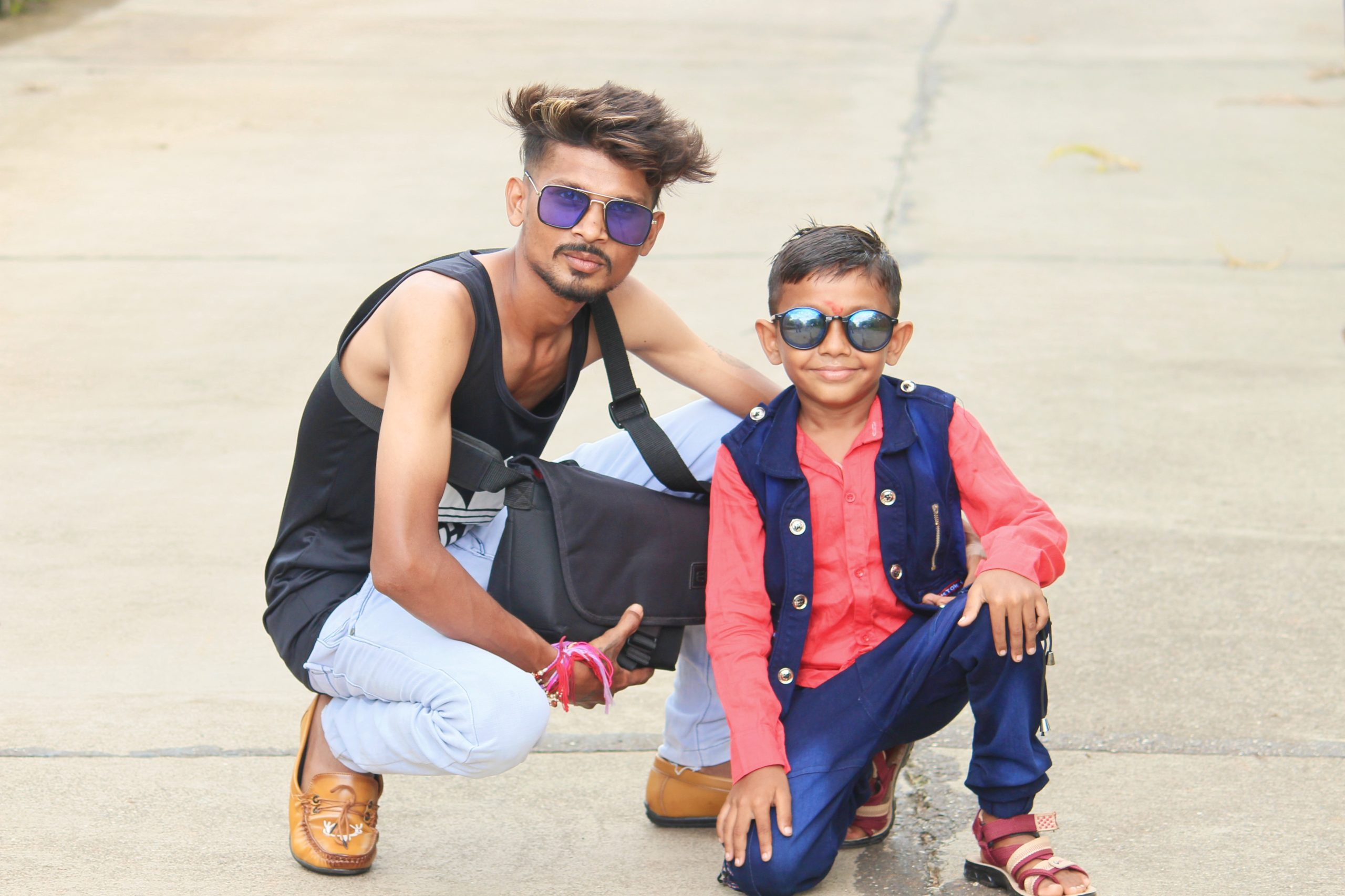 Two boys posing while wearing sunglasses