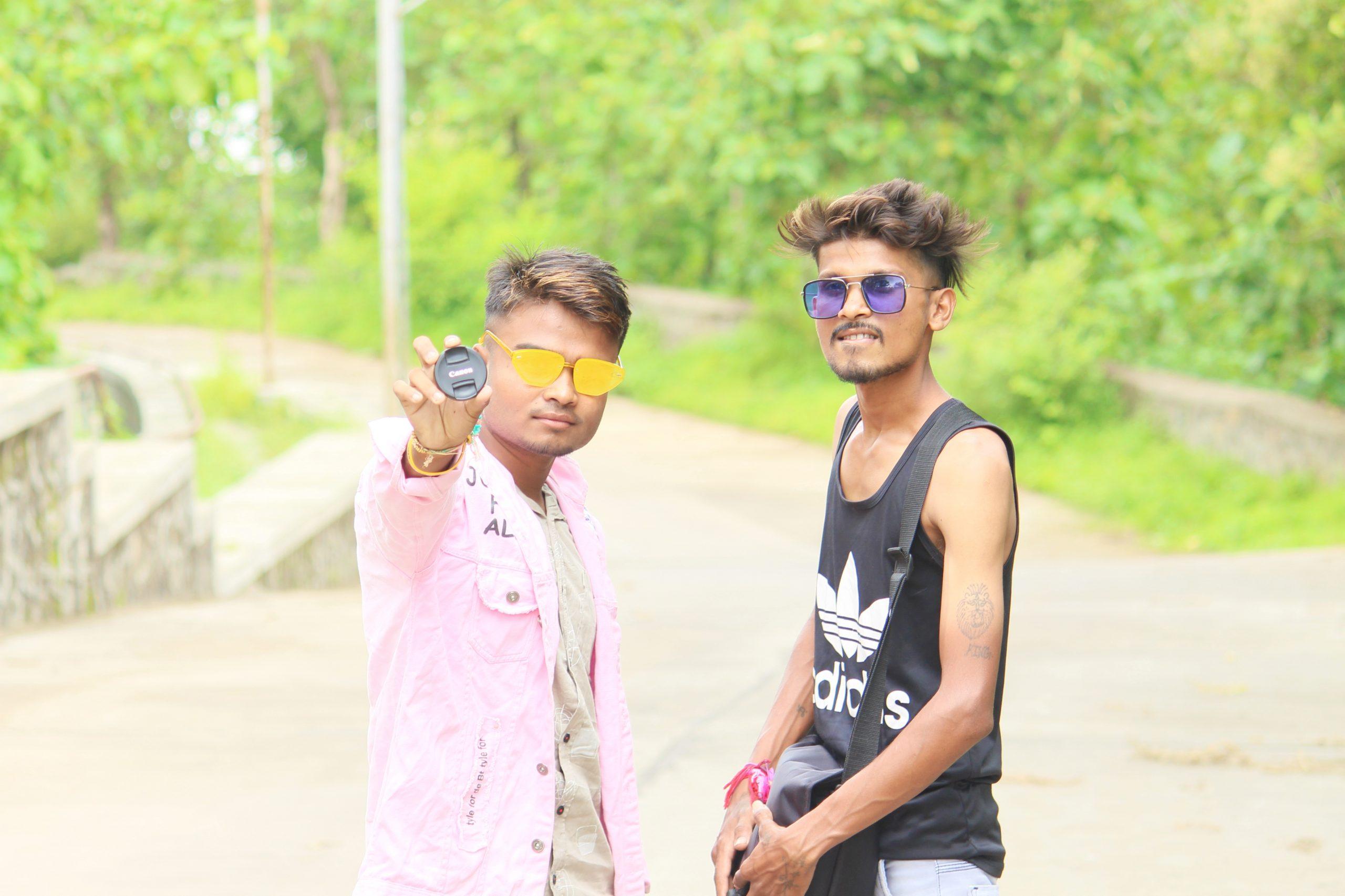Two model boy posing with camera lens cap