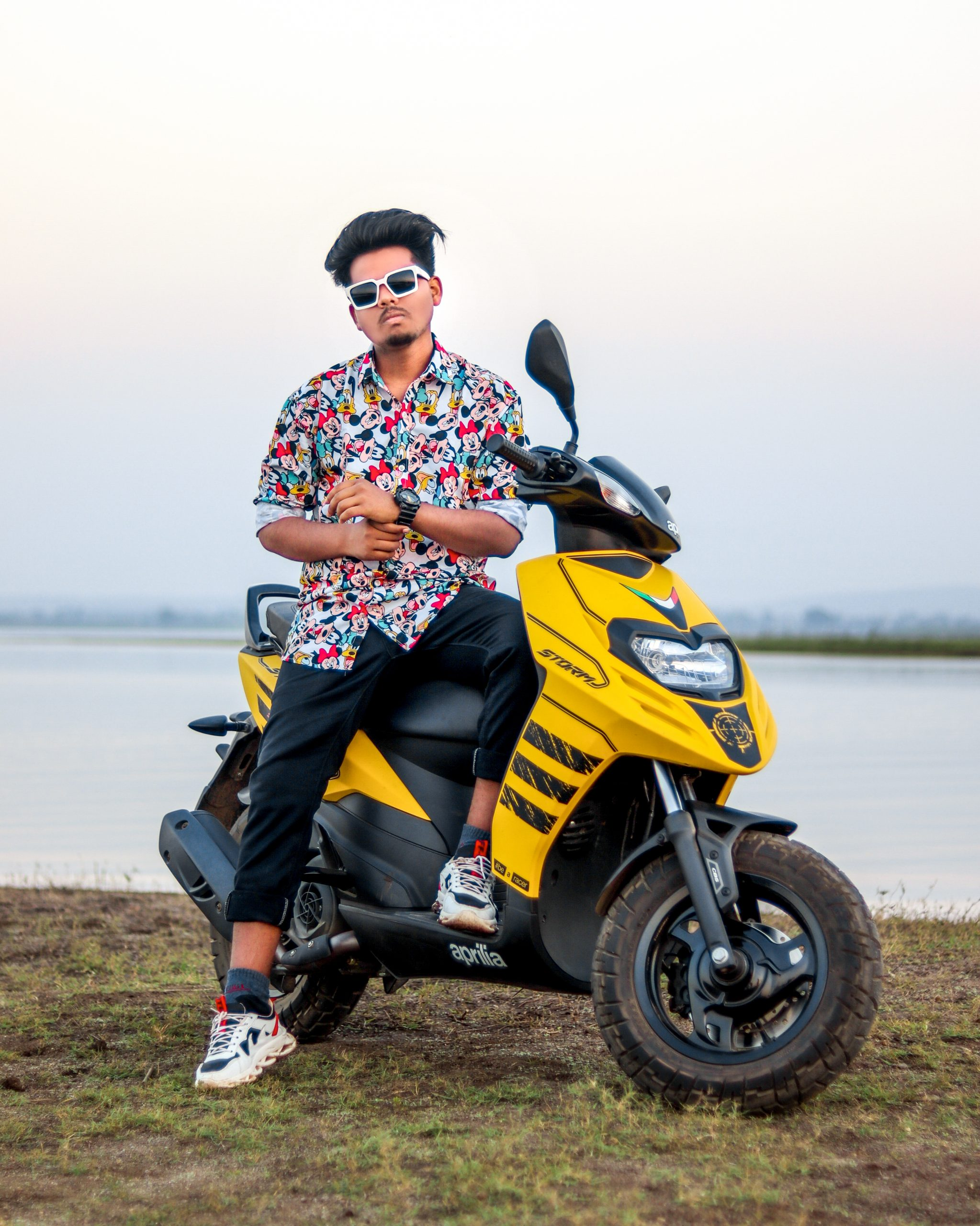 boy posing on scooty near the sea