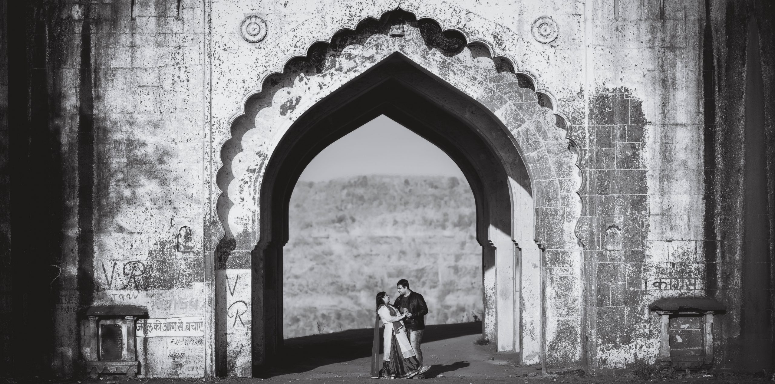 couple posing in front of palace entrance