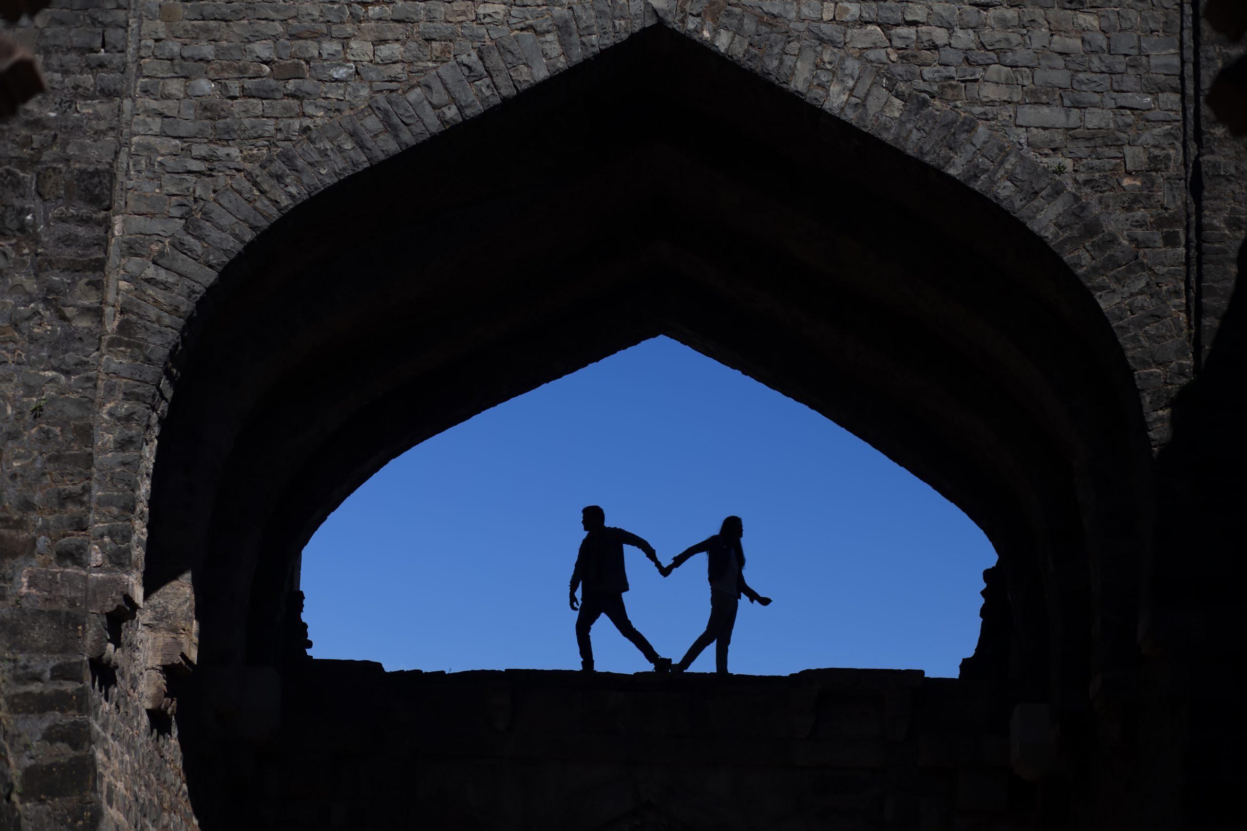 couple holding hand in dark