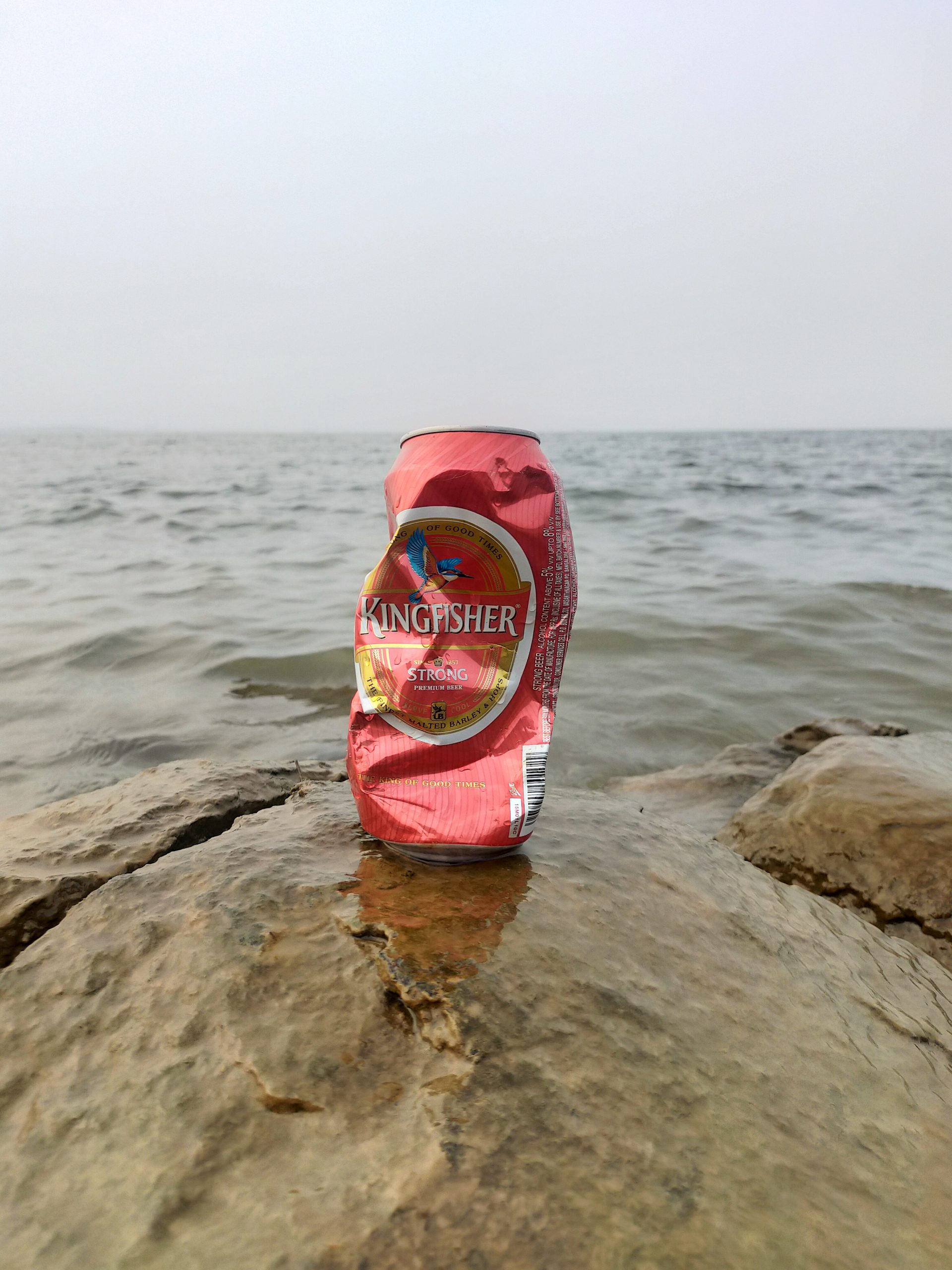 crashed kingfisher bottle on rock