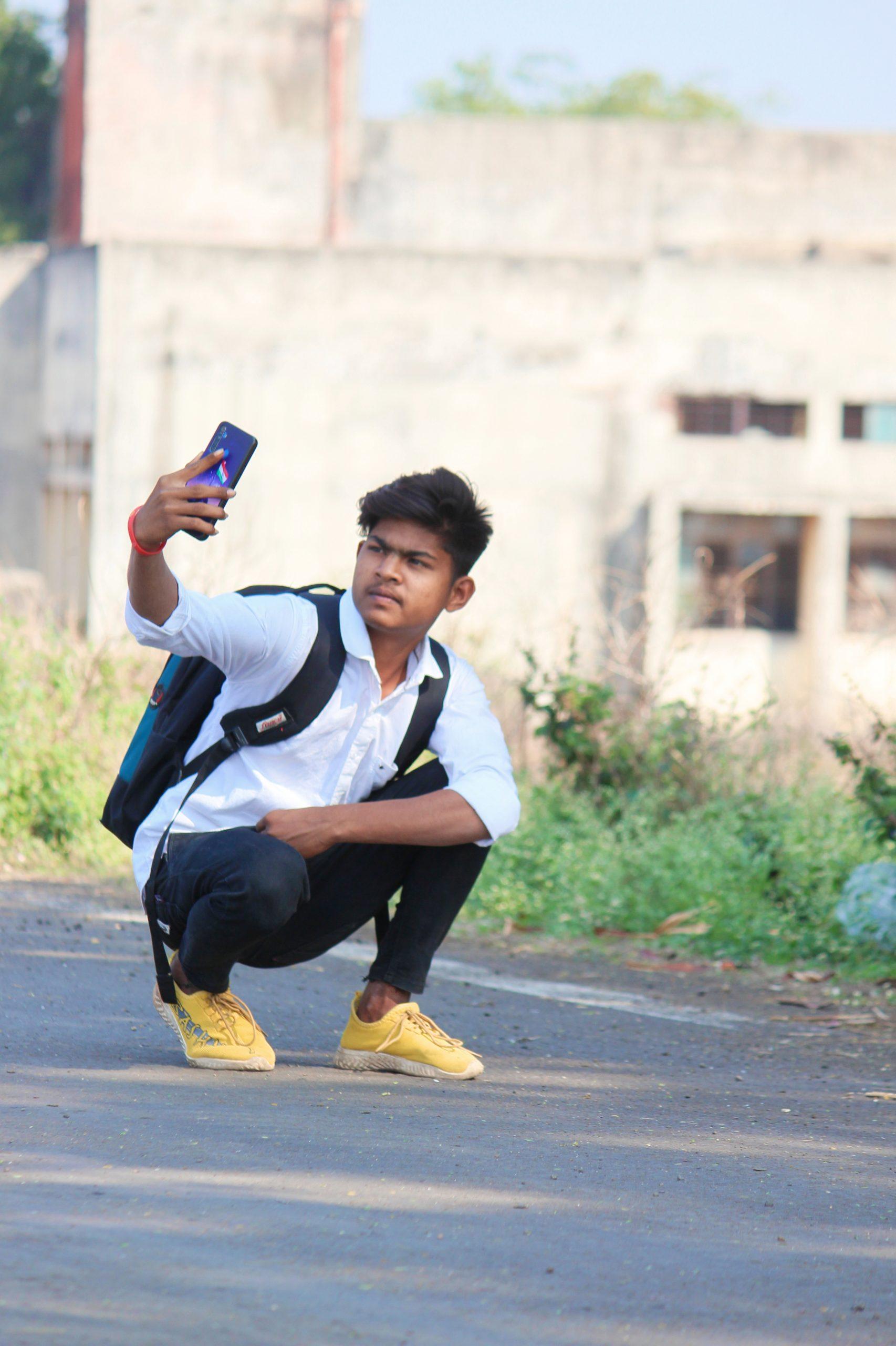 A boy taking selfie on road