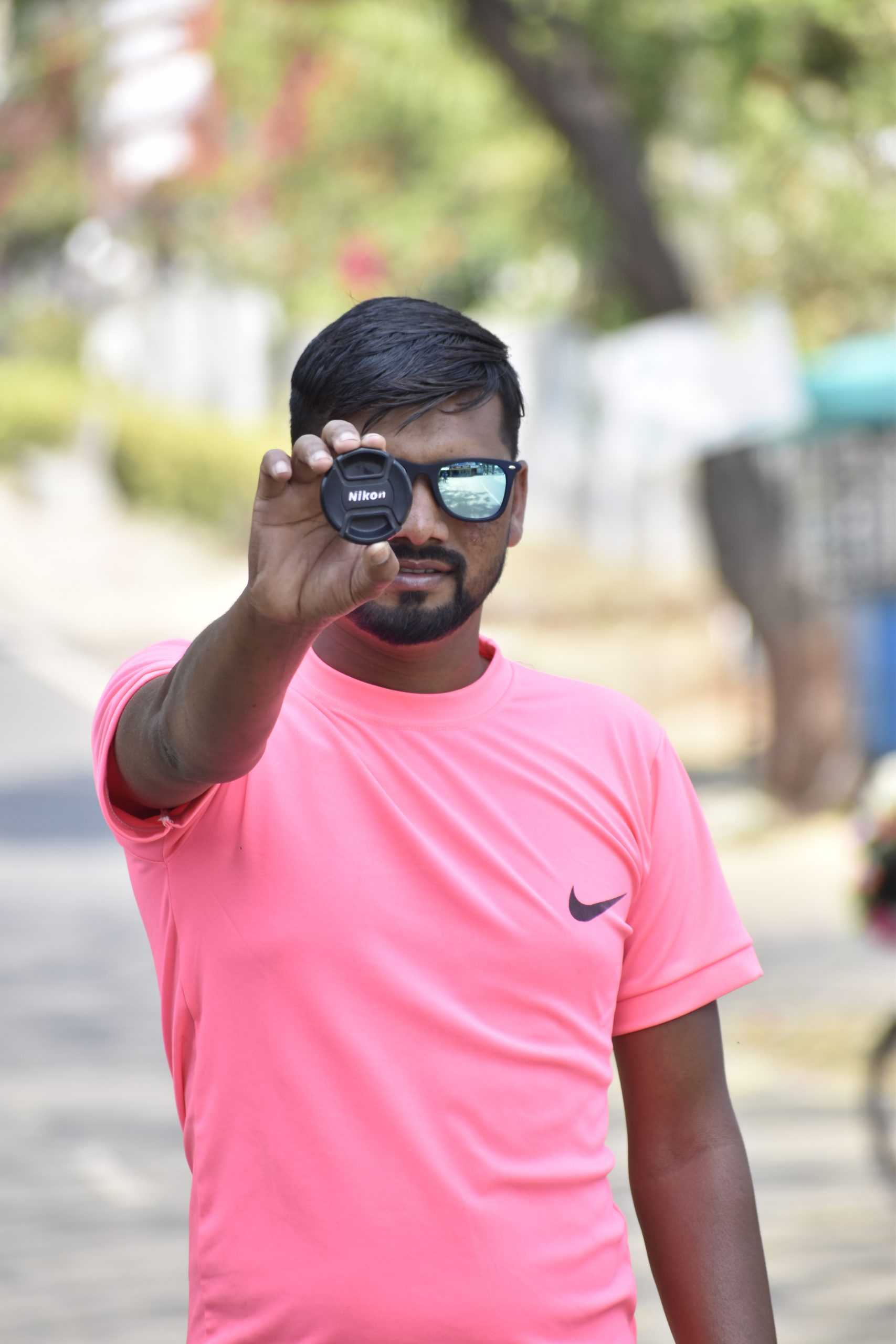 A boy showing camera lens cap