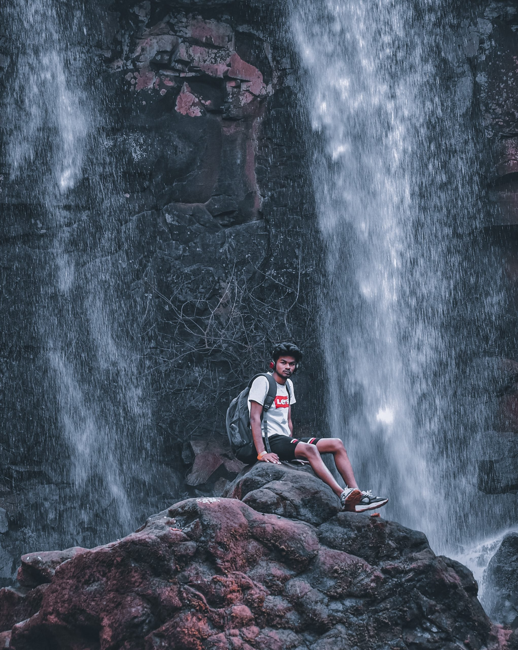 A boy sitting under a waterfall