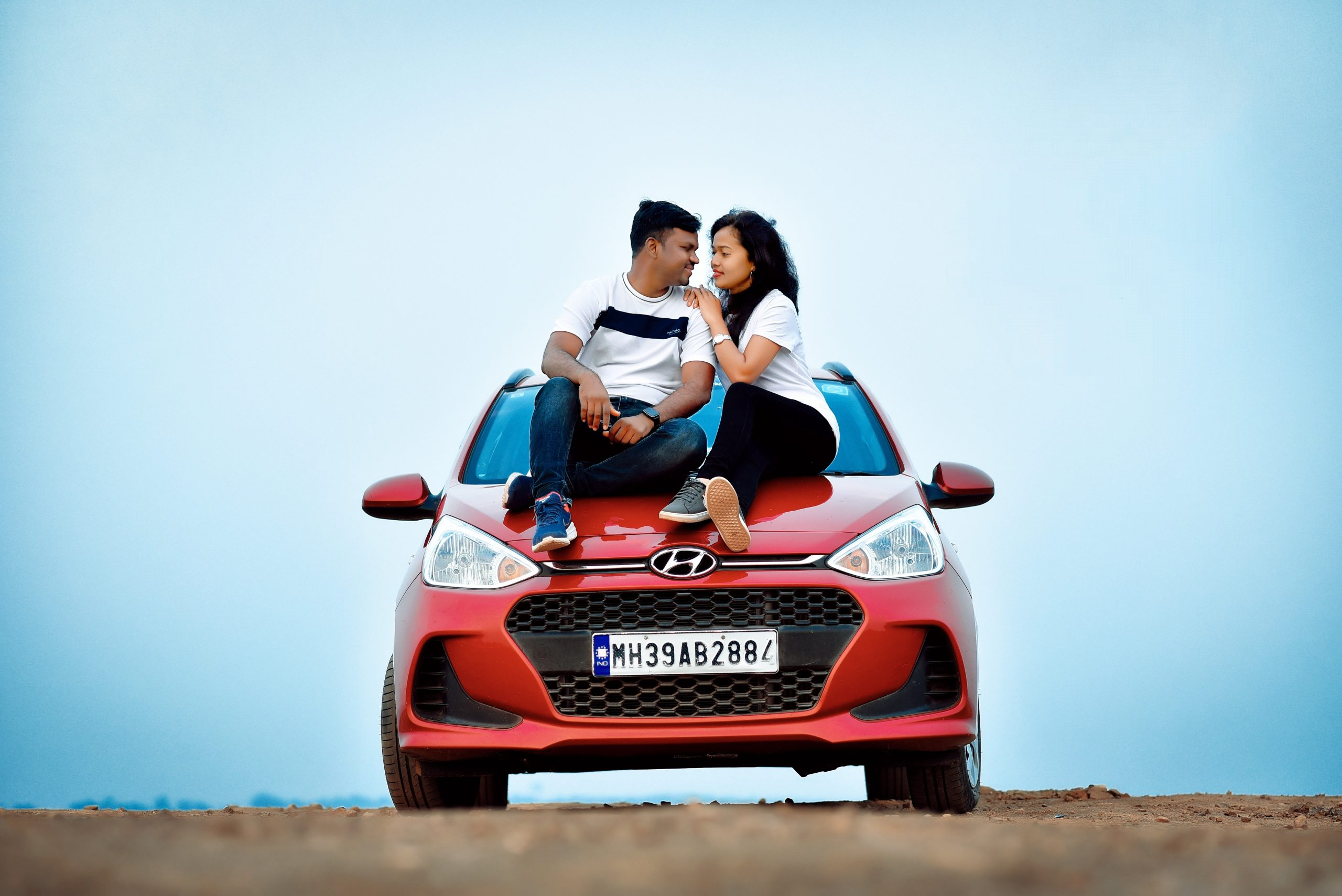 A young couple sitting on a car bonnet