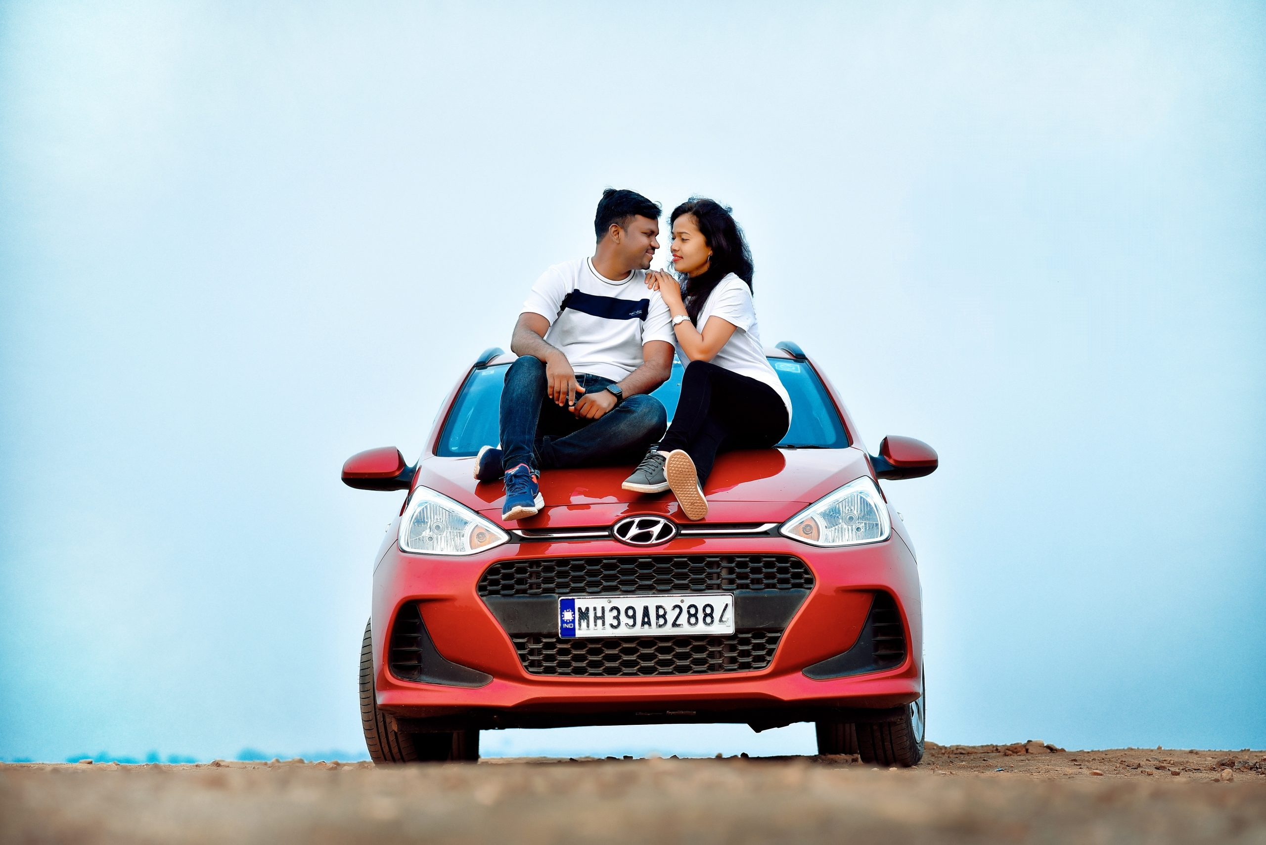 Photoshoot of couple sitting on a car
