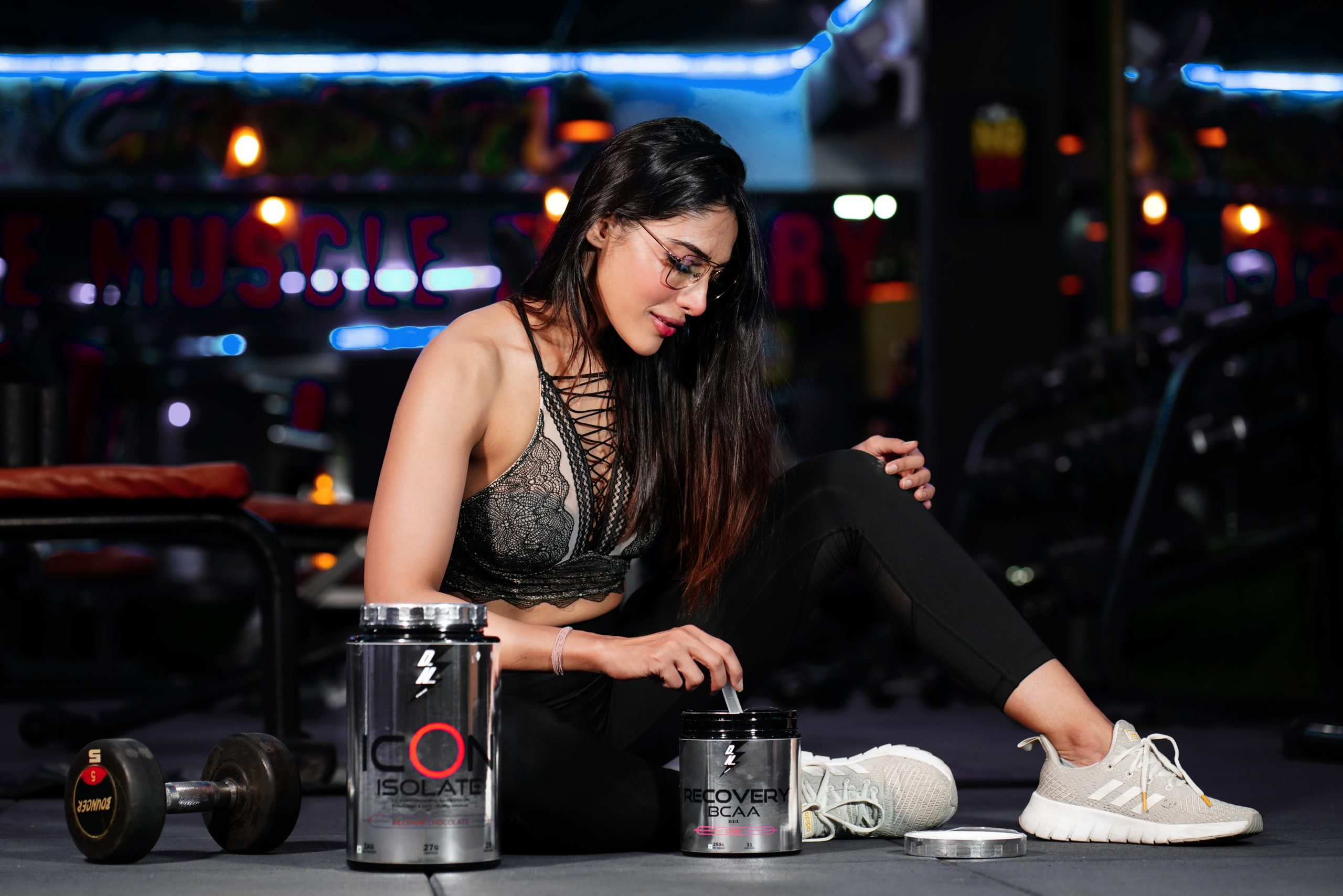 A fitness model preparing her supplements