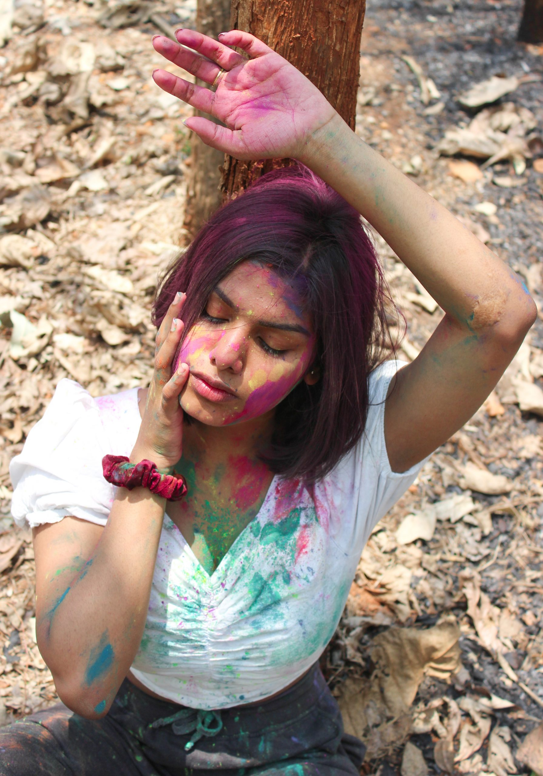 A girl applying holi colors on her face