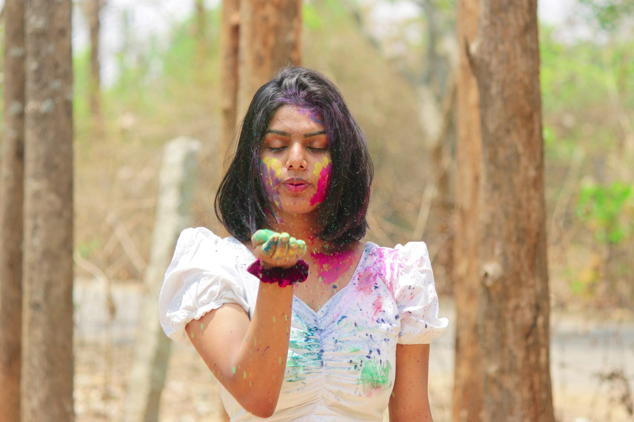 A girl celebrating Holi festival in a jungle