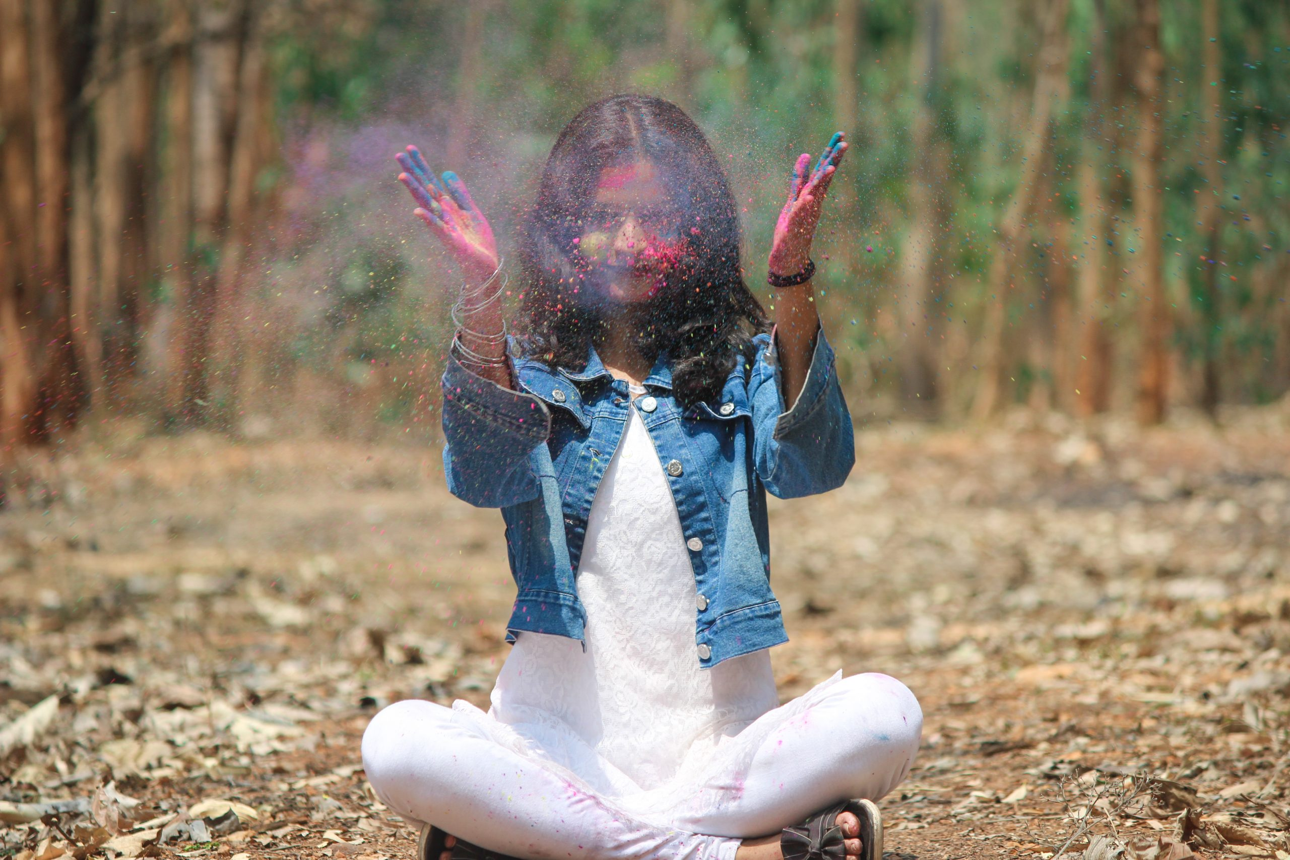 A girl in a jungle playing with Holi colors