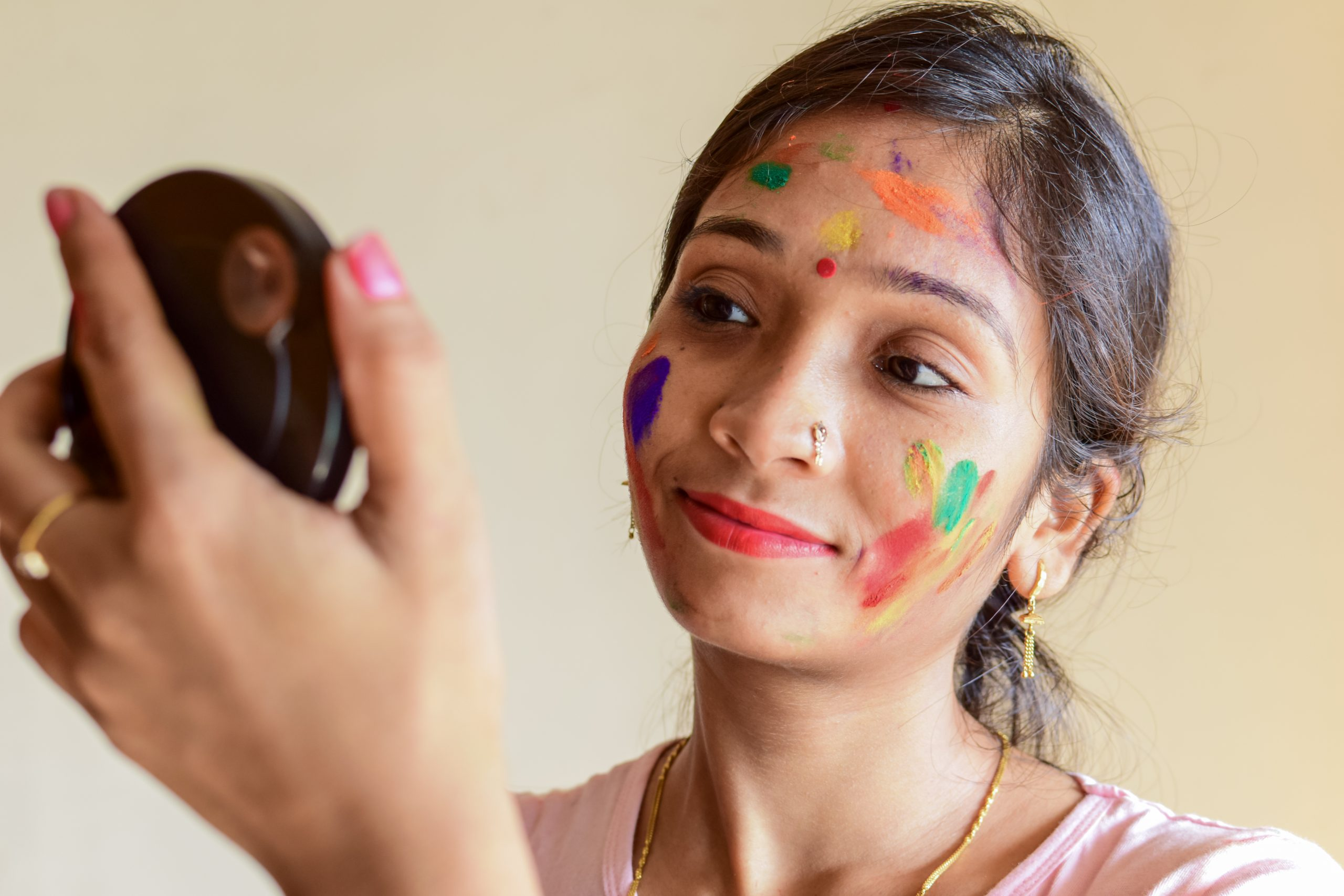 A girl seeing her colorful face in a mirror