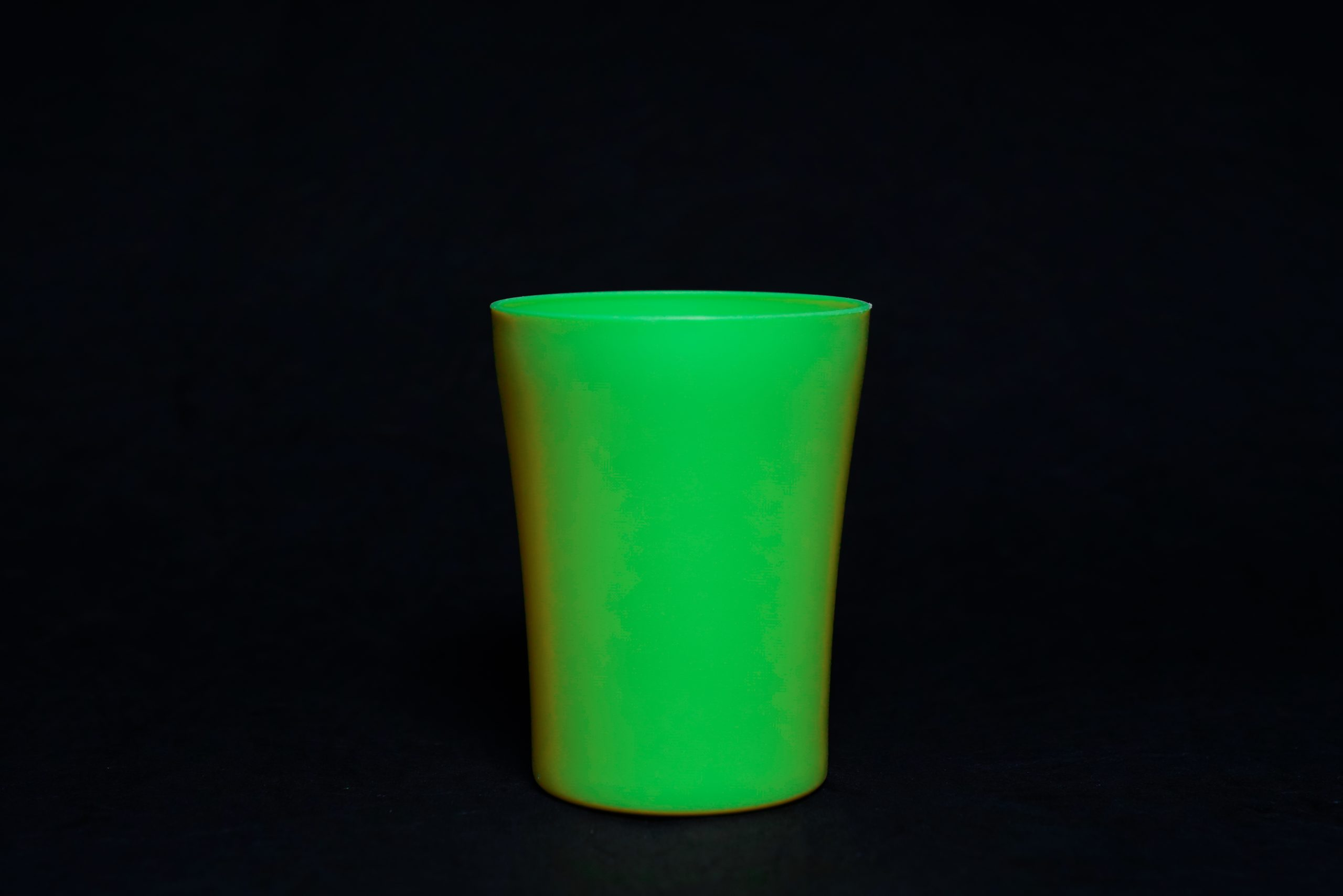A green glass with black background