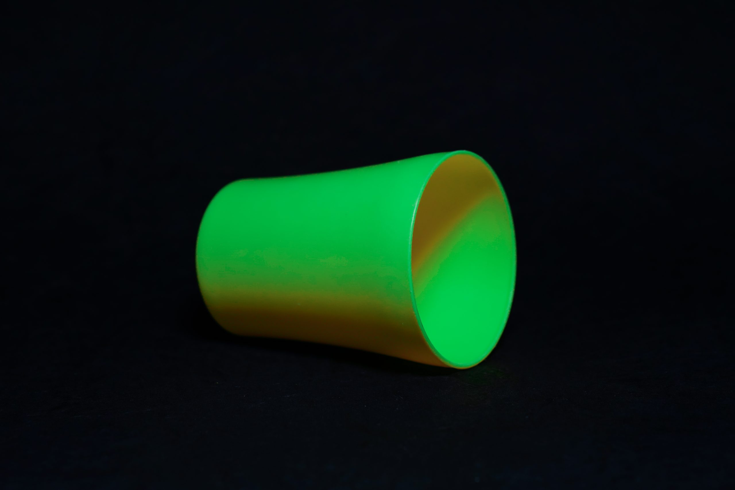 A green tumbler with black background