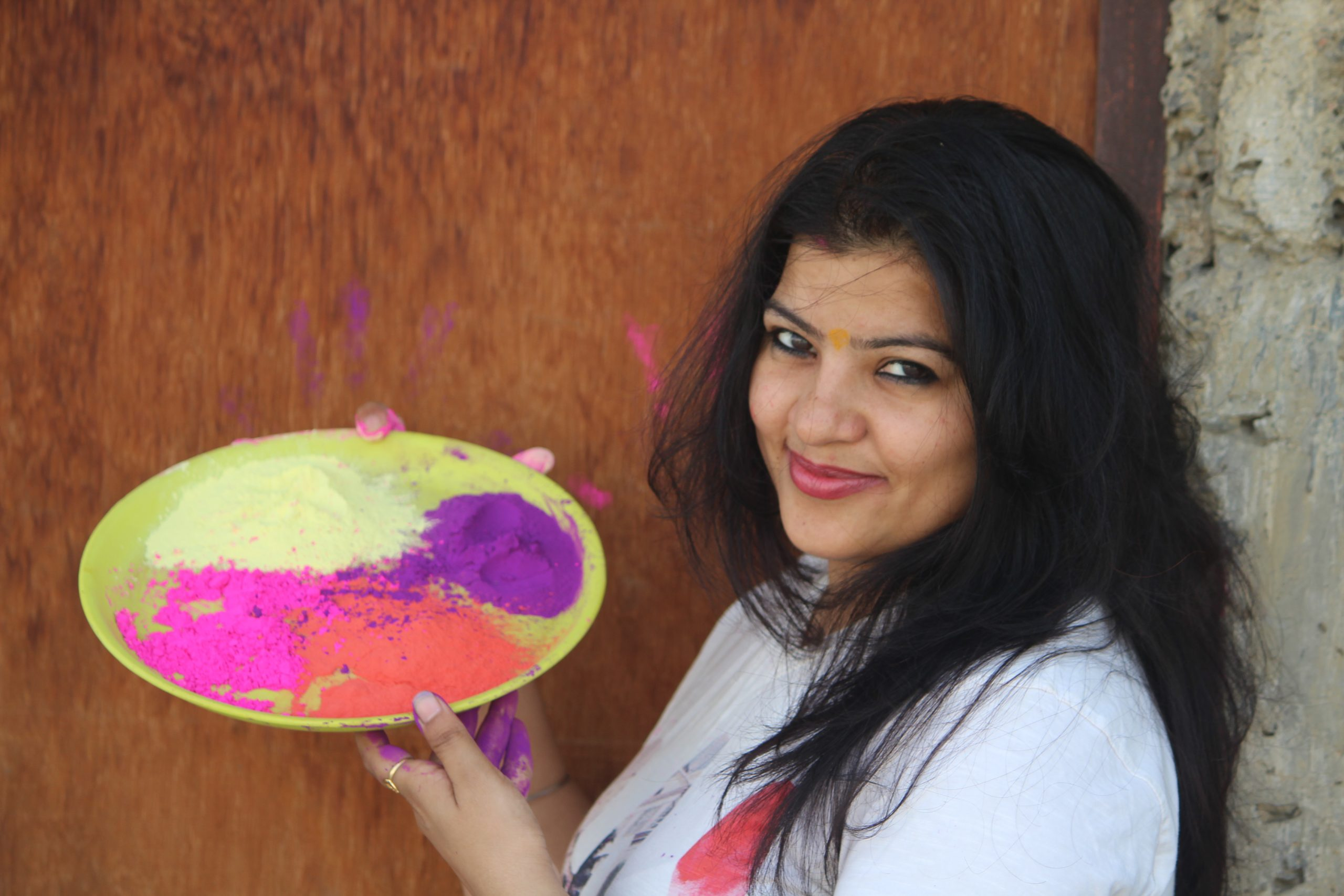 A happy girl holding a tray of holi colors