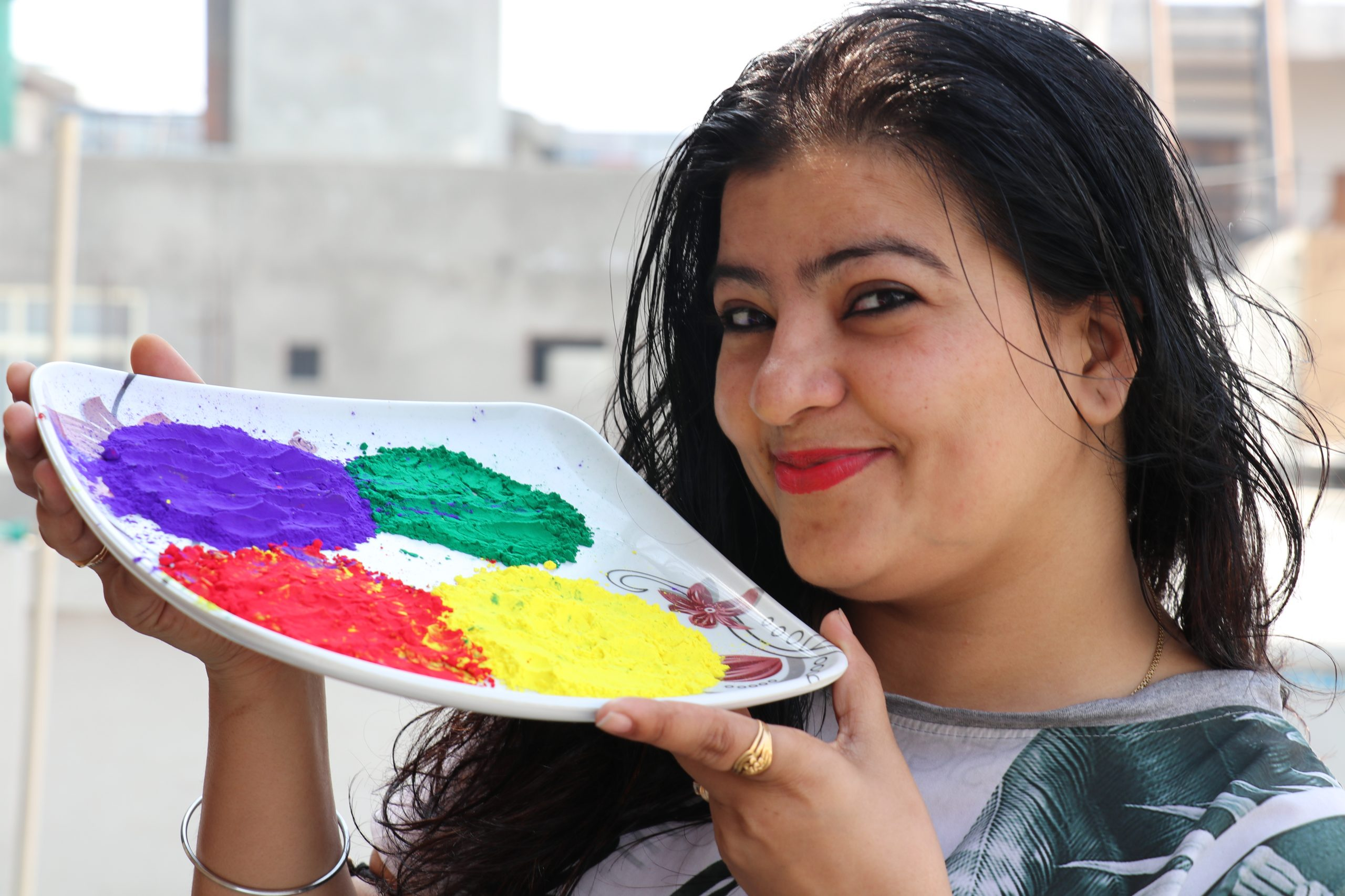 A happy woman with a tray of Holi colors