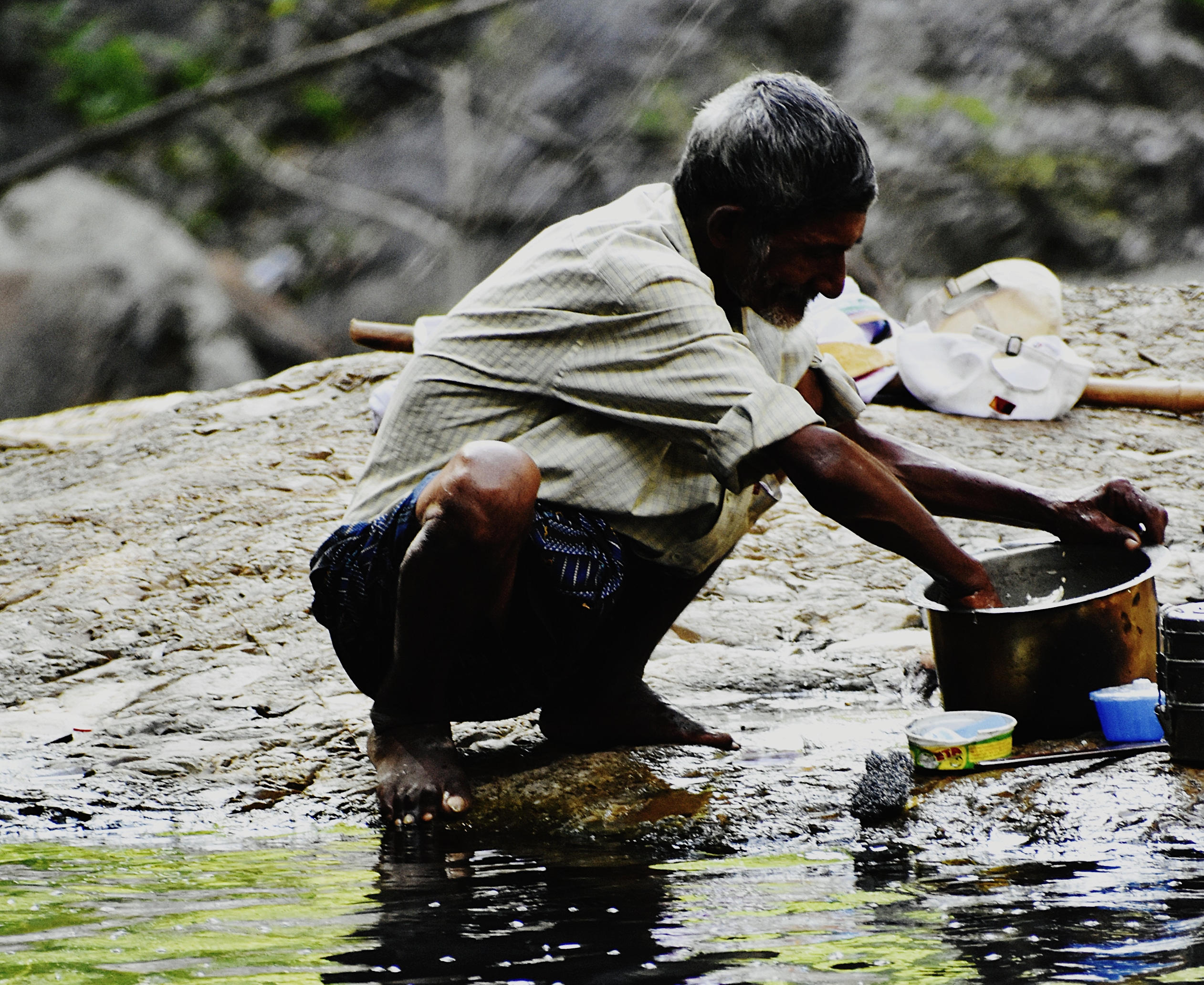 A man cleaning pots with river water