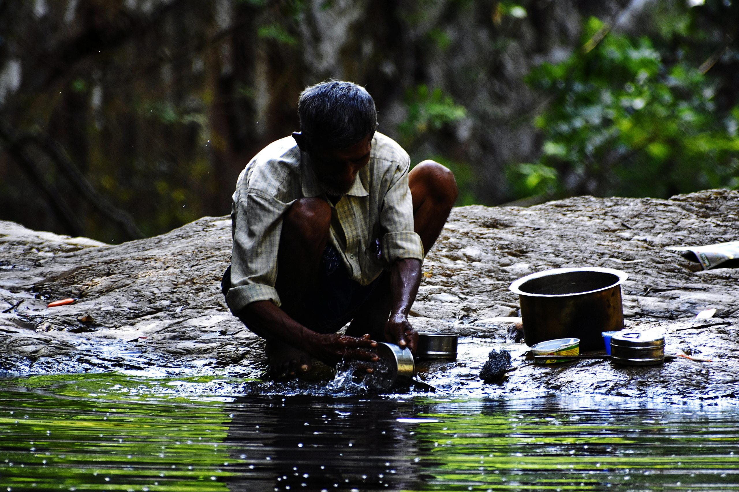 A man near river cleaning pots