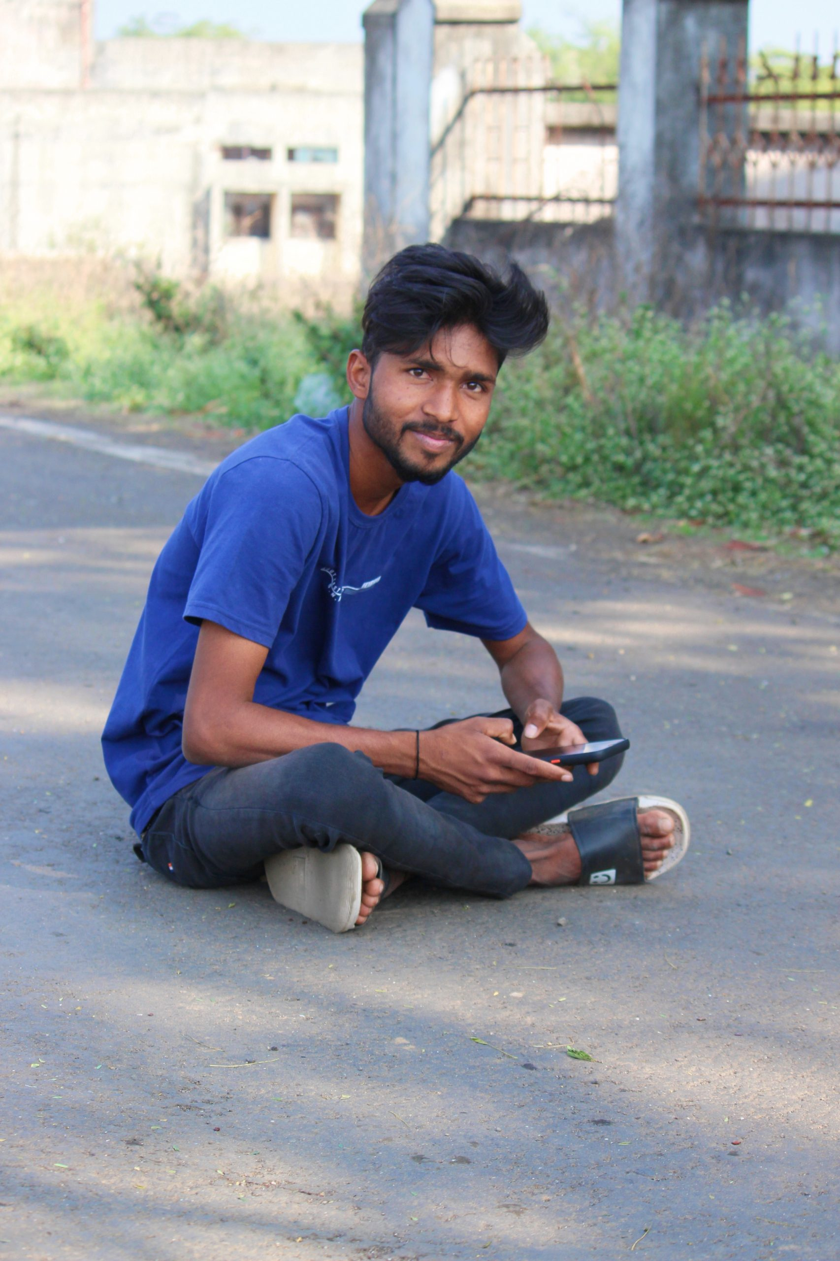 A street boy sitting on a road
