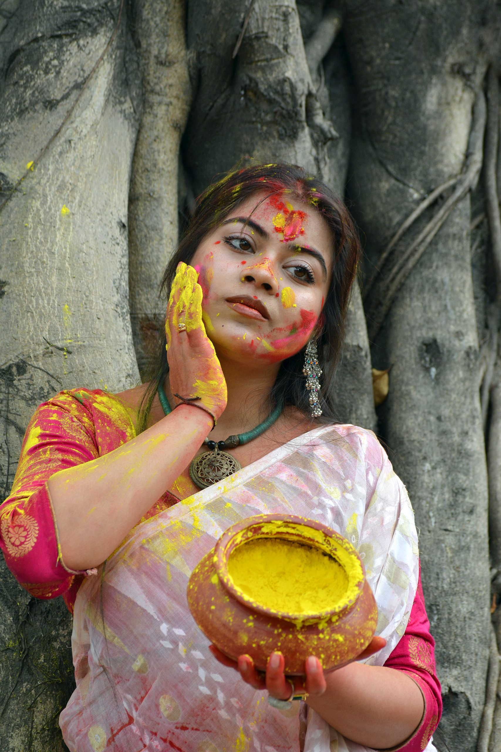 A woman applying Holi colors on her face