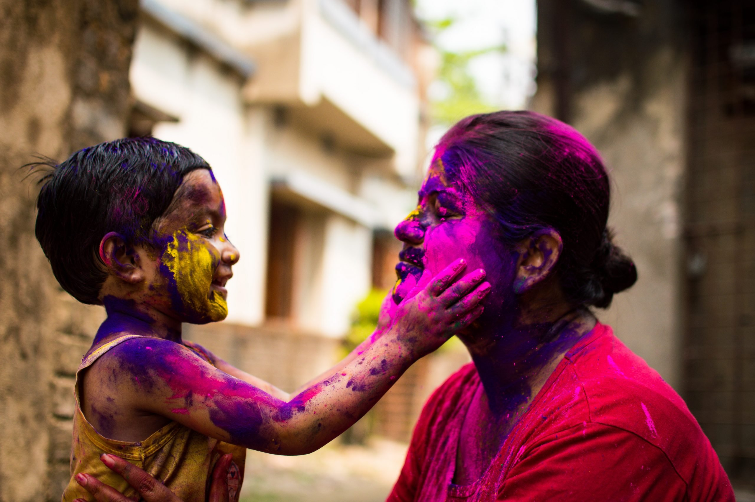 A woman celebrating Holi with her child