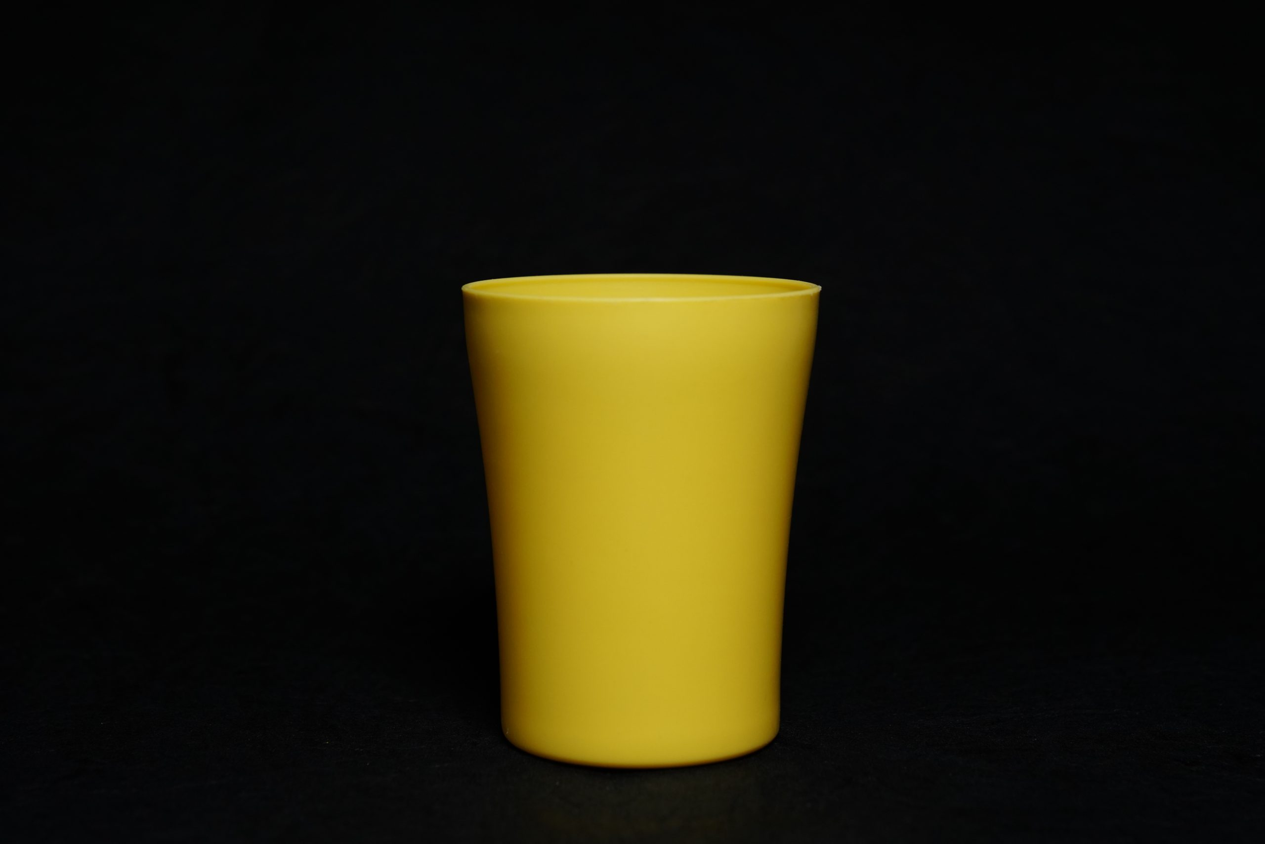 A yellow glass with black background